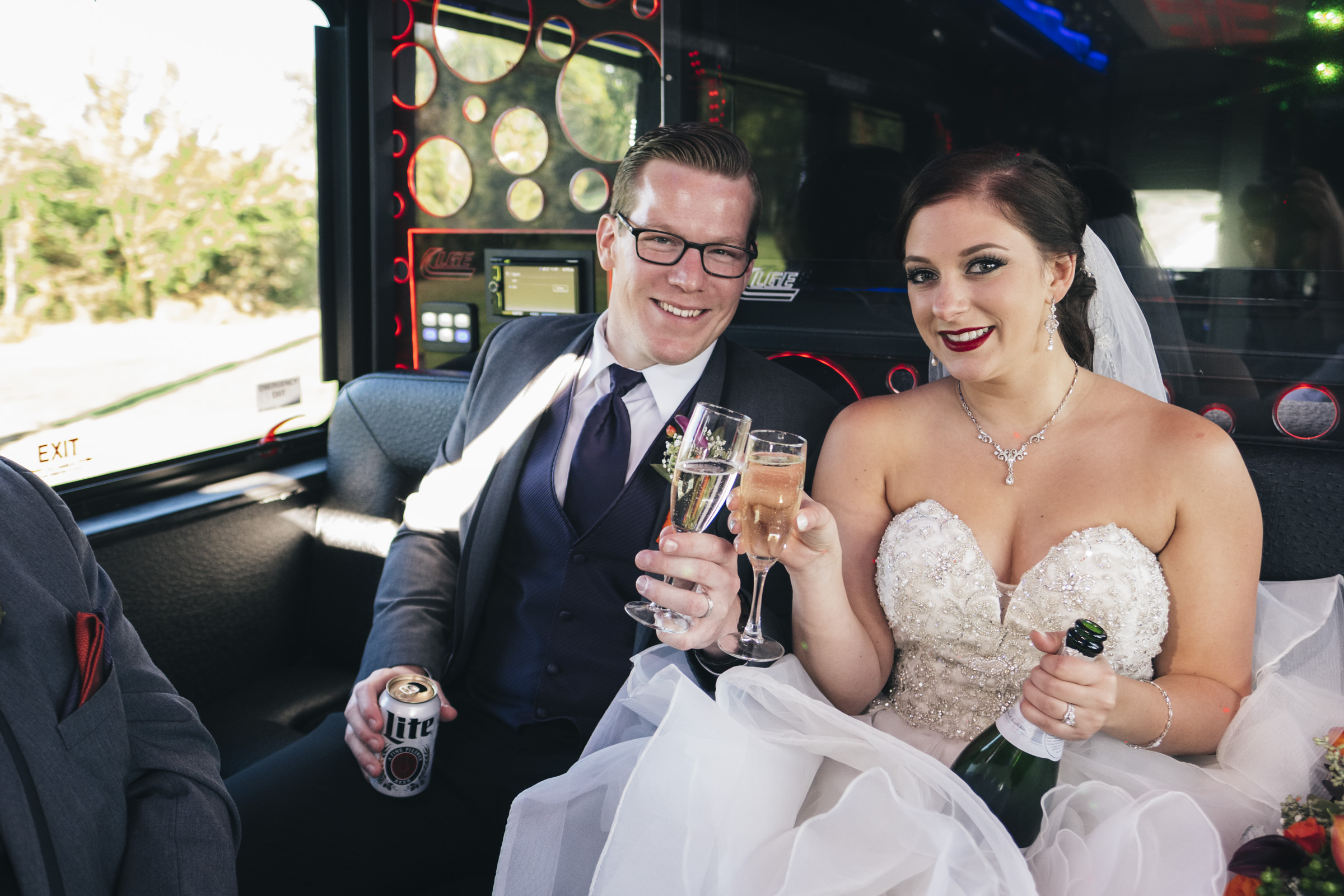 Bride and groom toast with champagne after wedding in party bus.