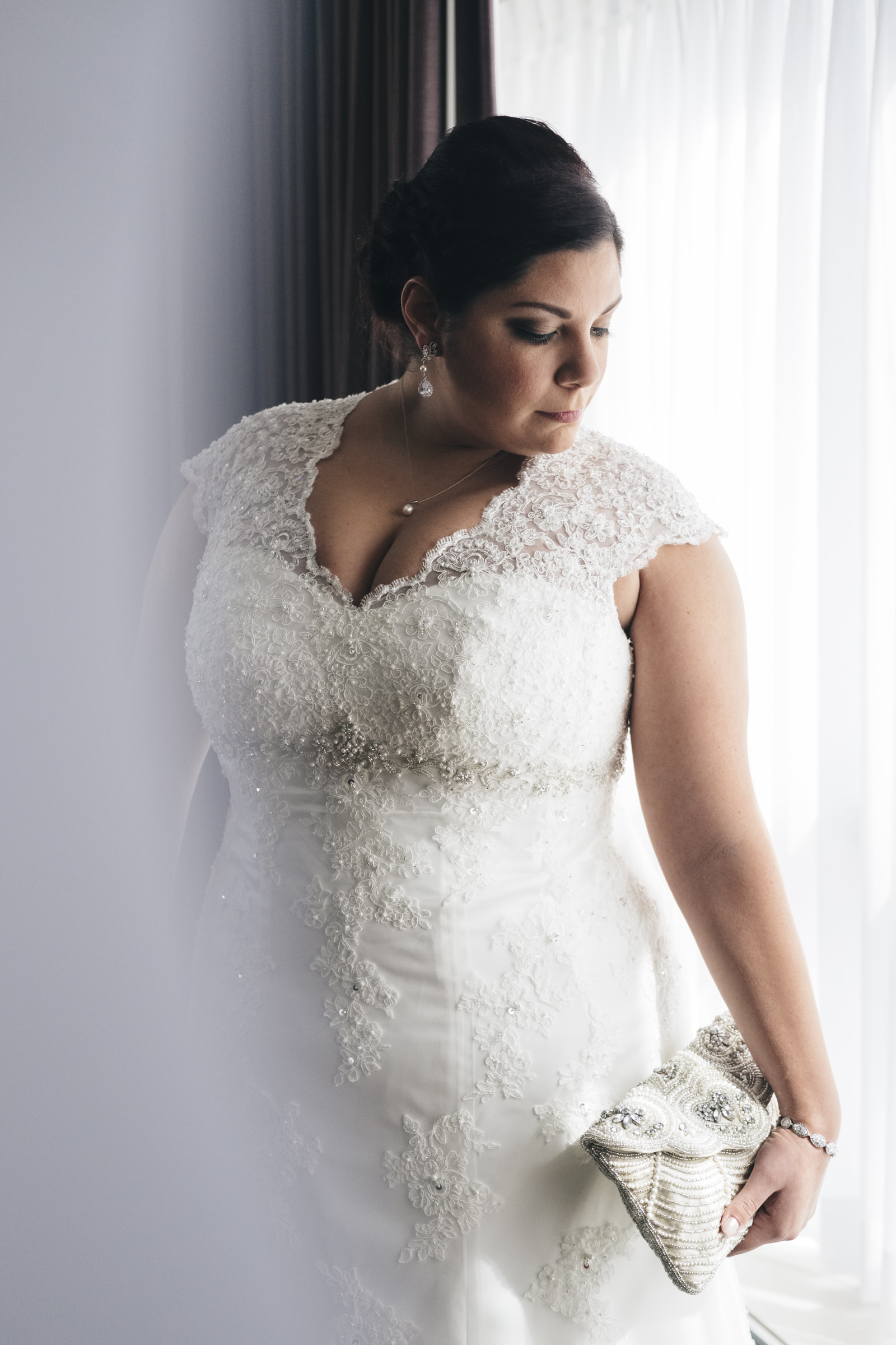 Bride stands in the window of The Park Inn Hotel in downtown Toledo on her wedding day.