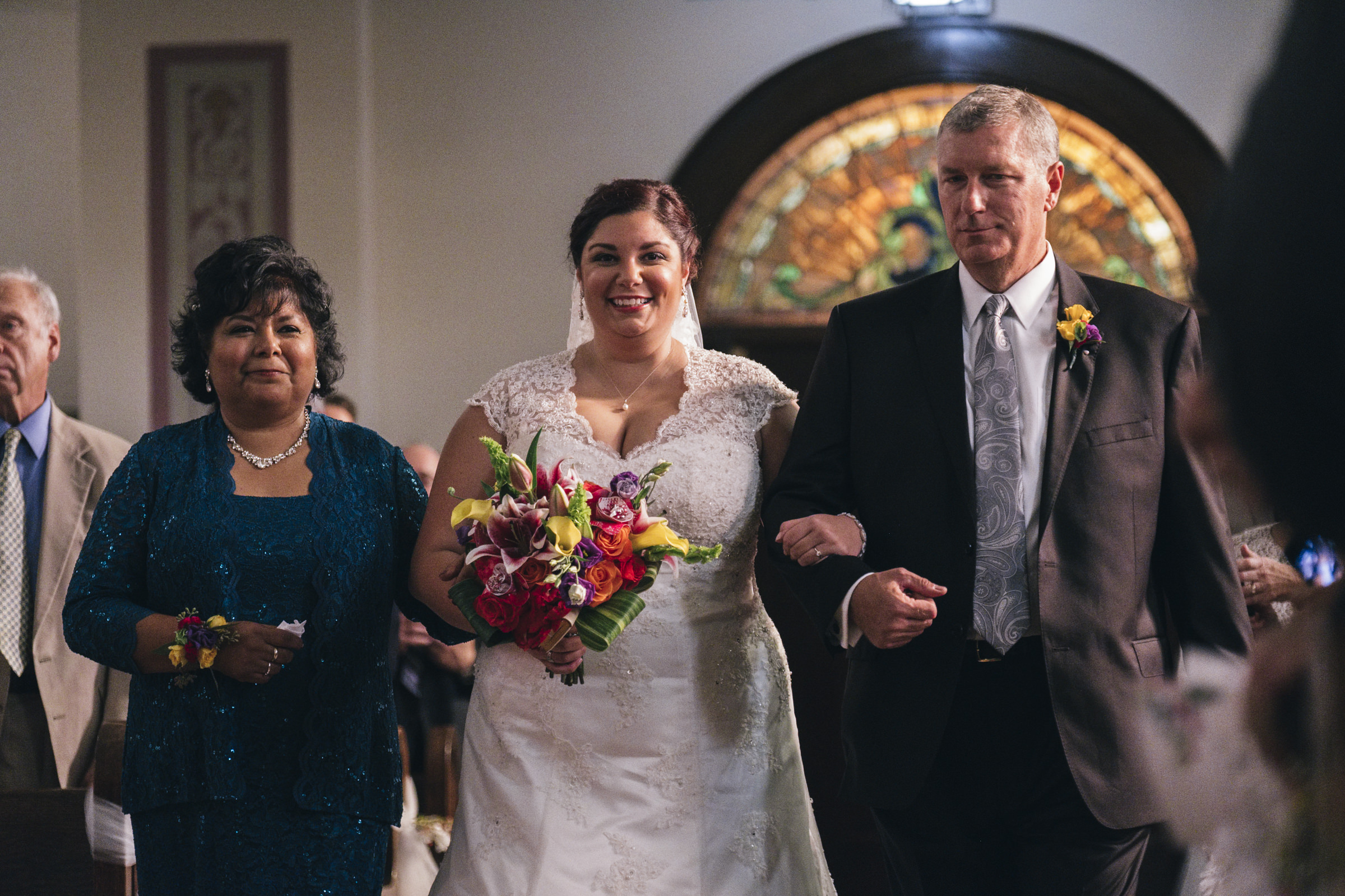 Bride is walked down the aisle by both her mom and dad in Irish and Hispanic wedding in downtown Toledo