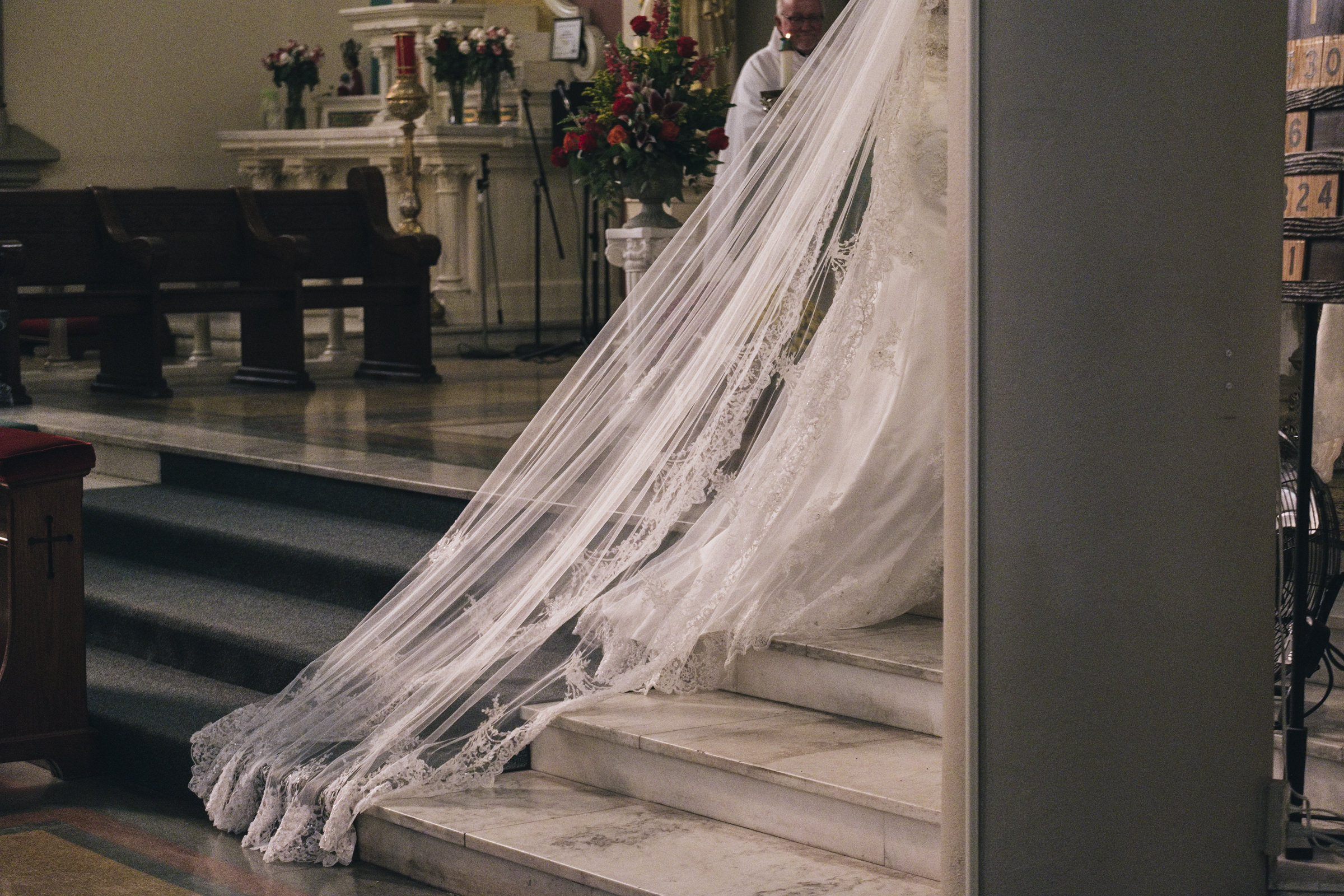 The bride's long wedding veil is lace and drags on the ground during her Catholic Irish Hispanic wedding ceremony,