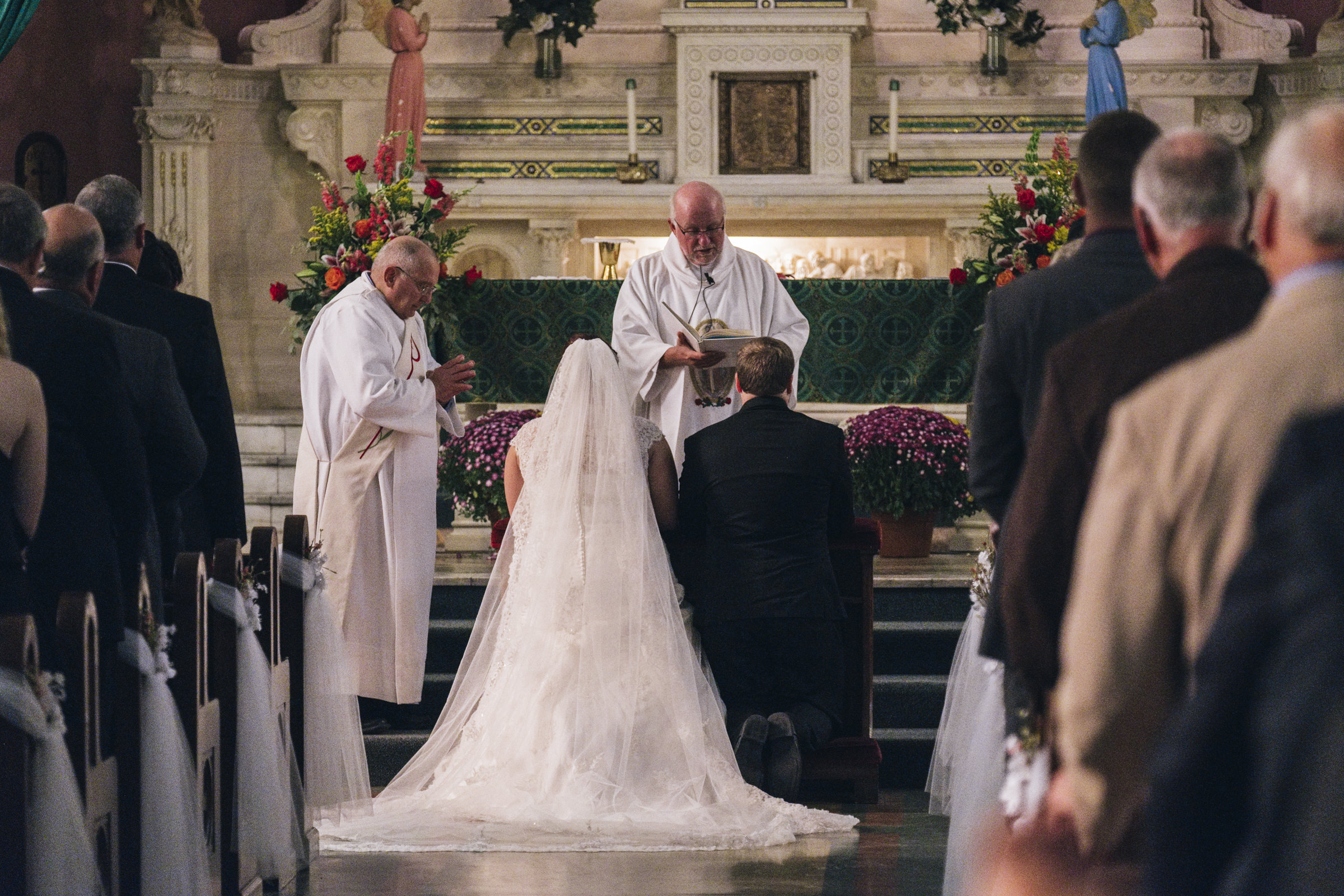 Bride and groom kneel at alter in honor of Hispanic wedding tradition