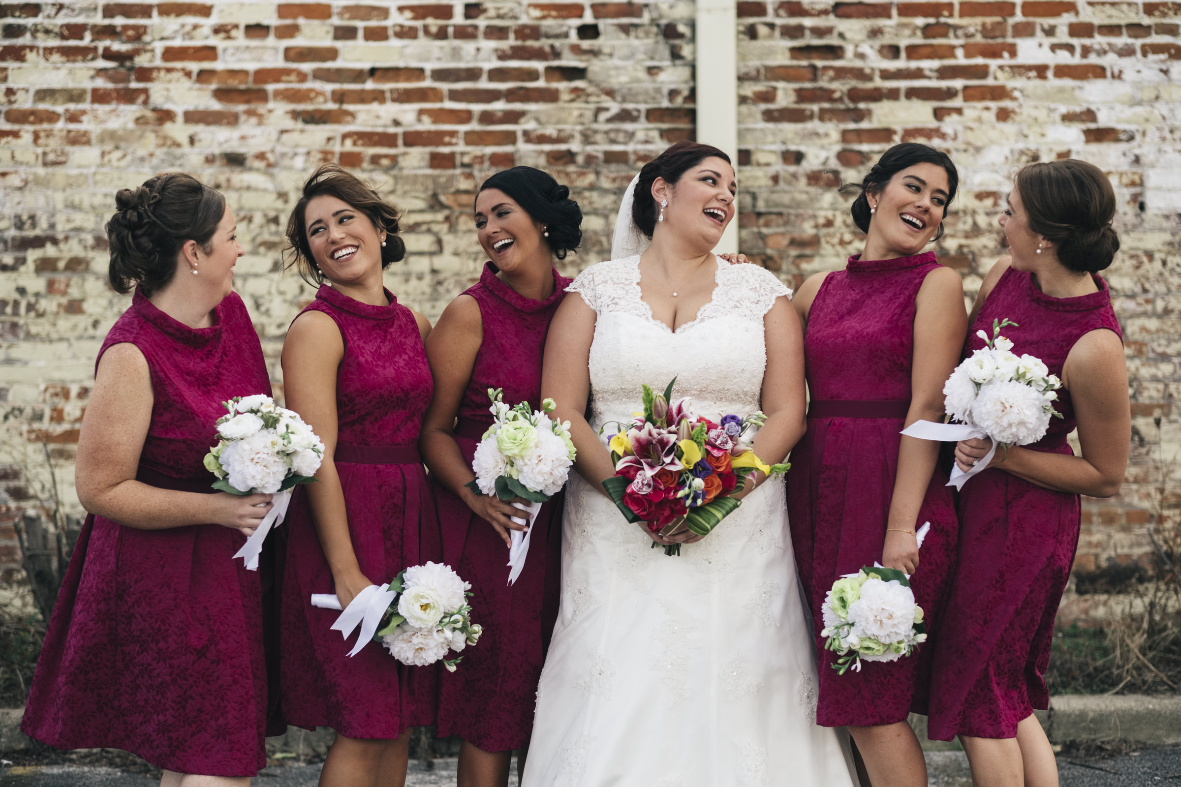 Bridesmaids stand around the bride and laugh on her wedding day,