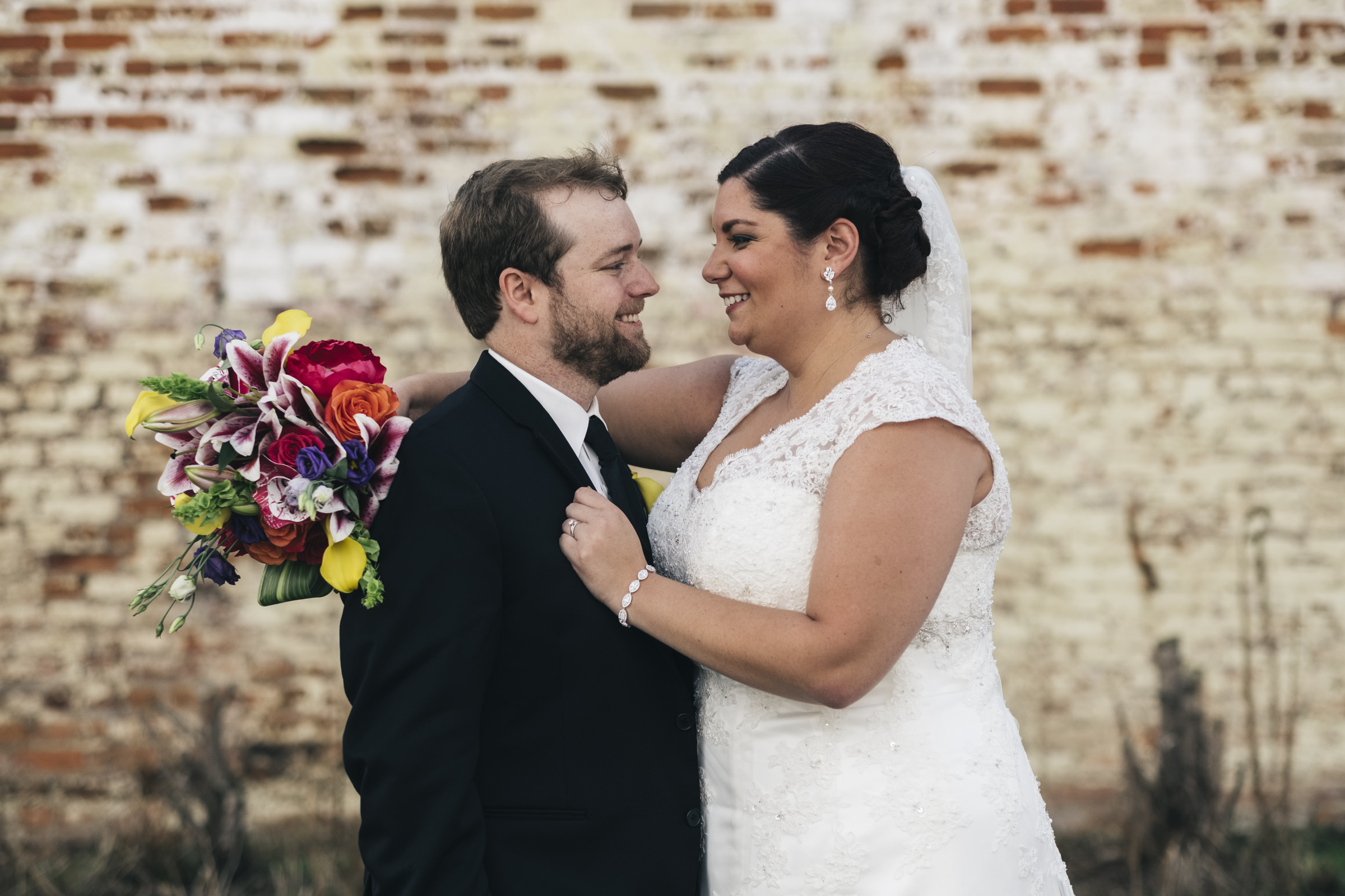 Bride and groom share an intimate moment during their photo session outside a warehouse in Toledo Ohio