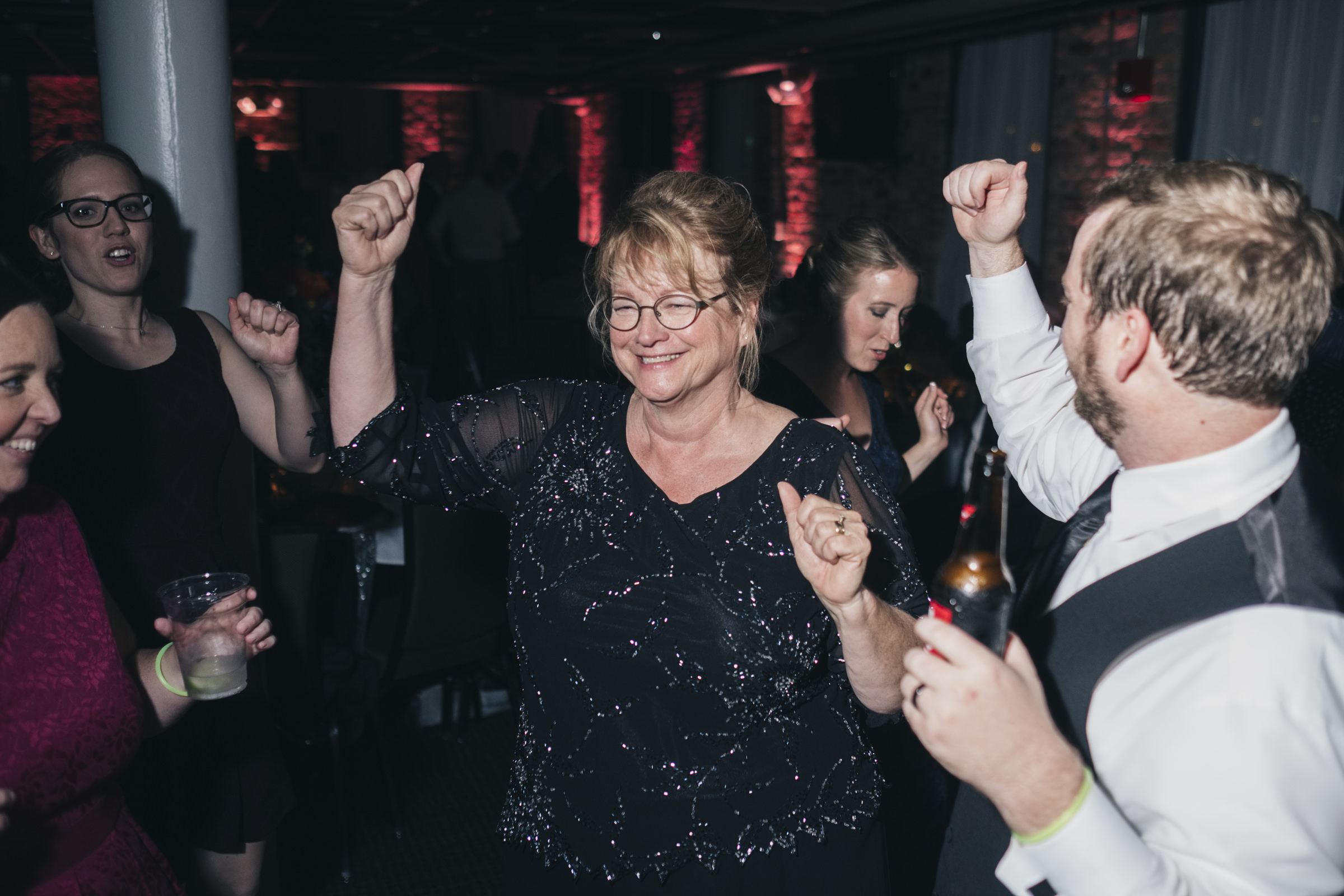 Mother of the bride dances at her son's wedding reception.