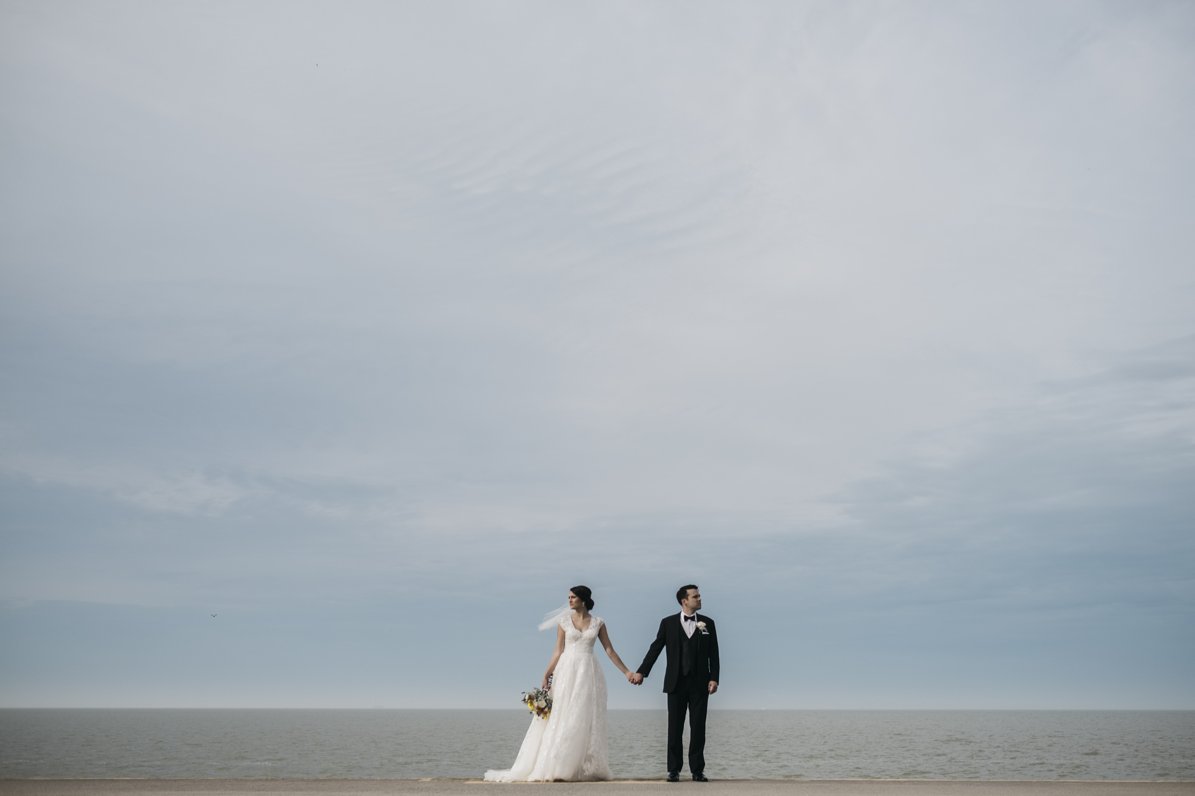 Bride and groom stand of the edge of the water at Maumee Bay State Park Wedding