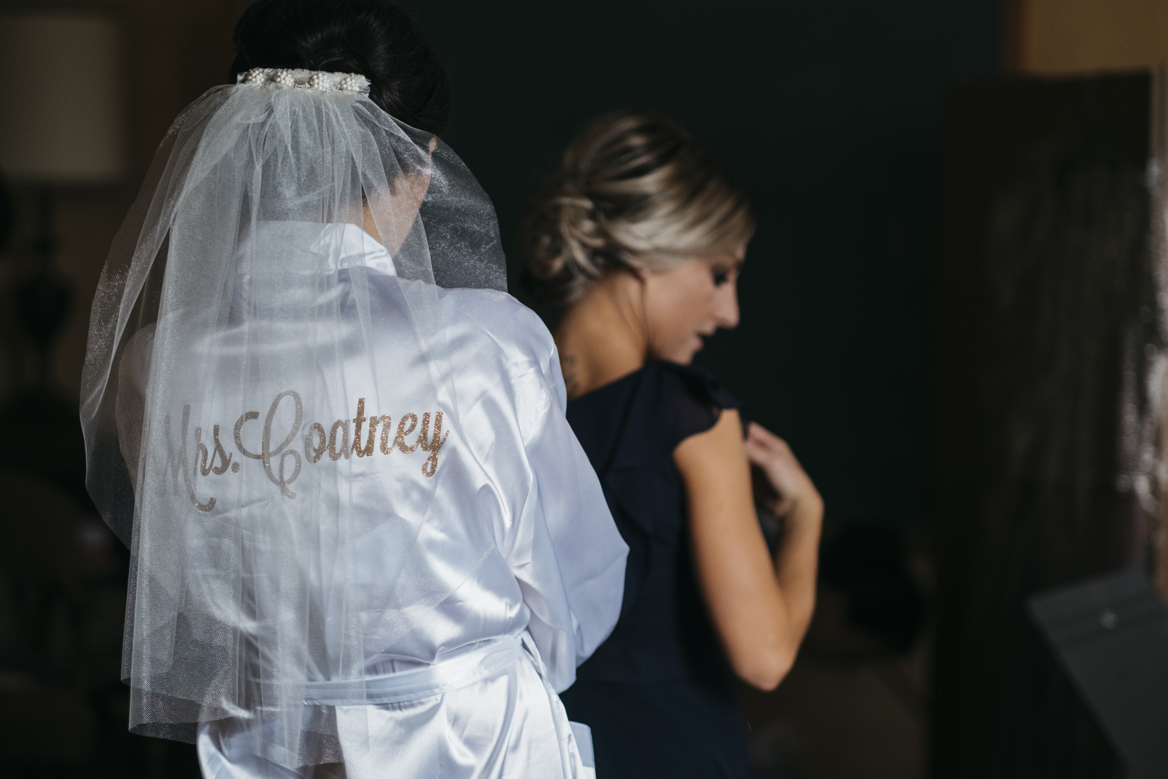The bride wears her custom robe while she helps her bridesmaid get into her dress before the wedding ceremony in Fremont Ohio