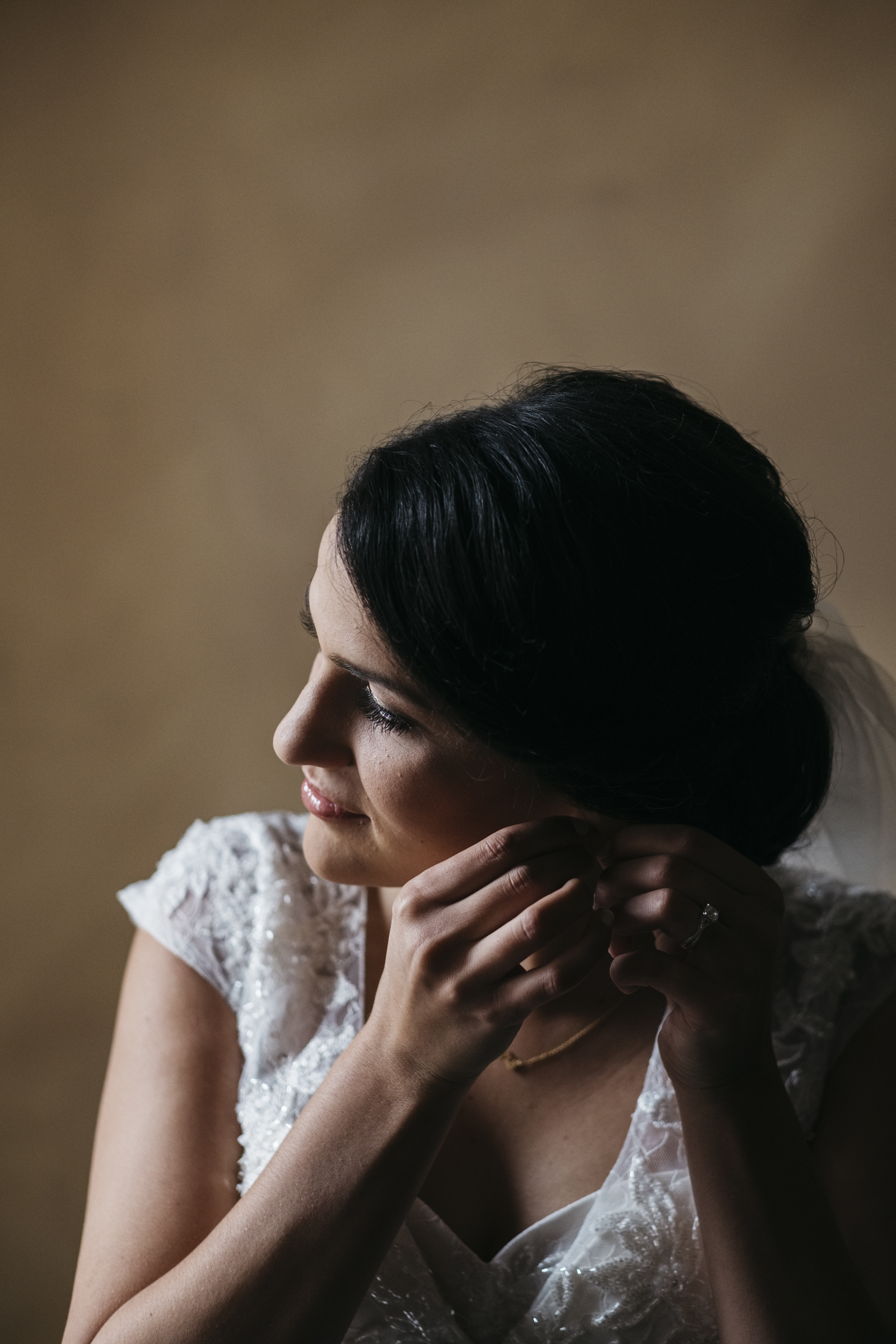 Bride fixes her earrings before her wedding ceremony at Fremont church in Ohio