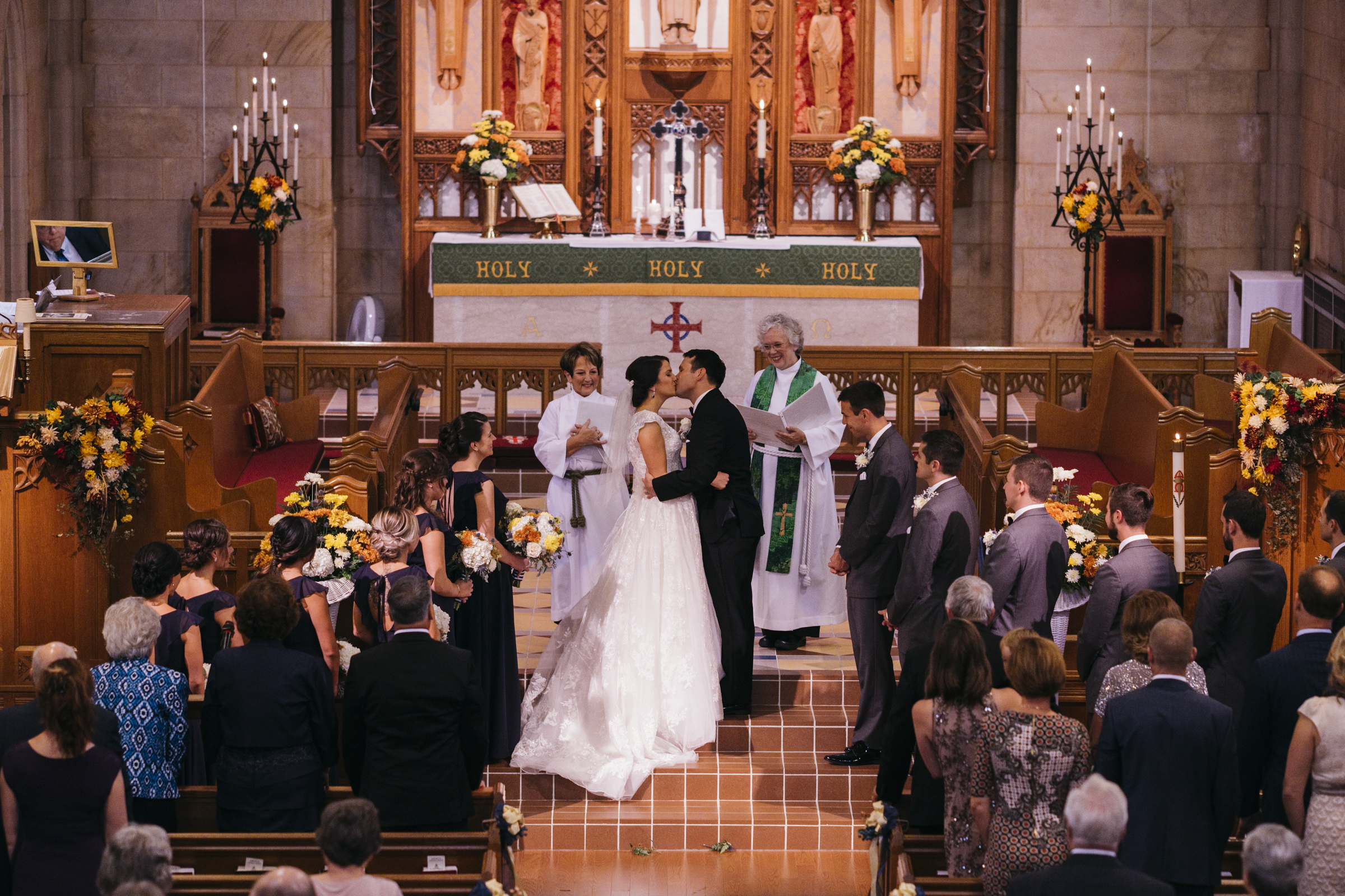 Bride and groom share a kiss on the alter of Grace Lutheran Church as husband and wife on their wedding day