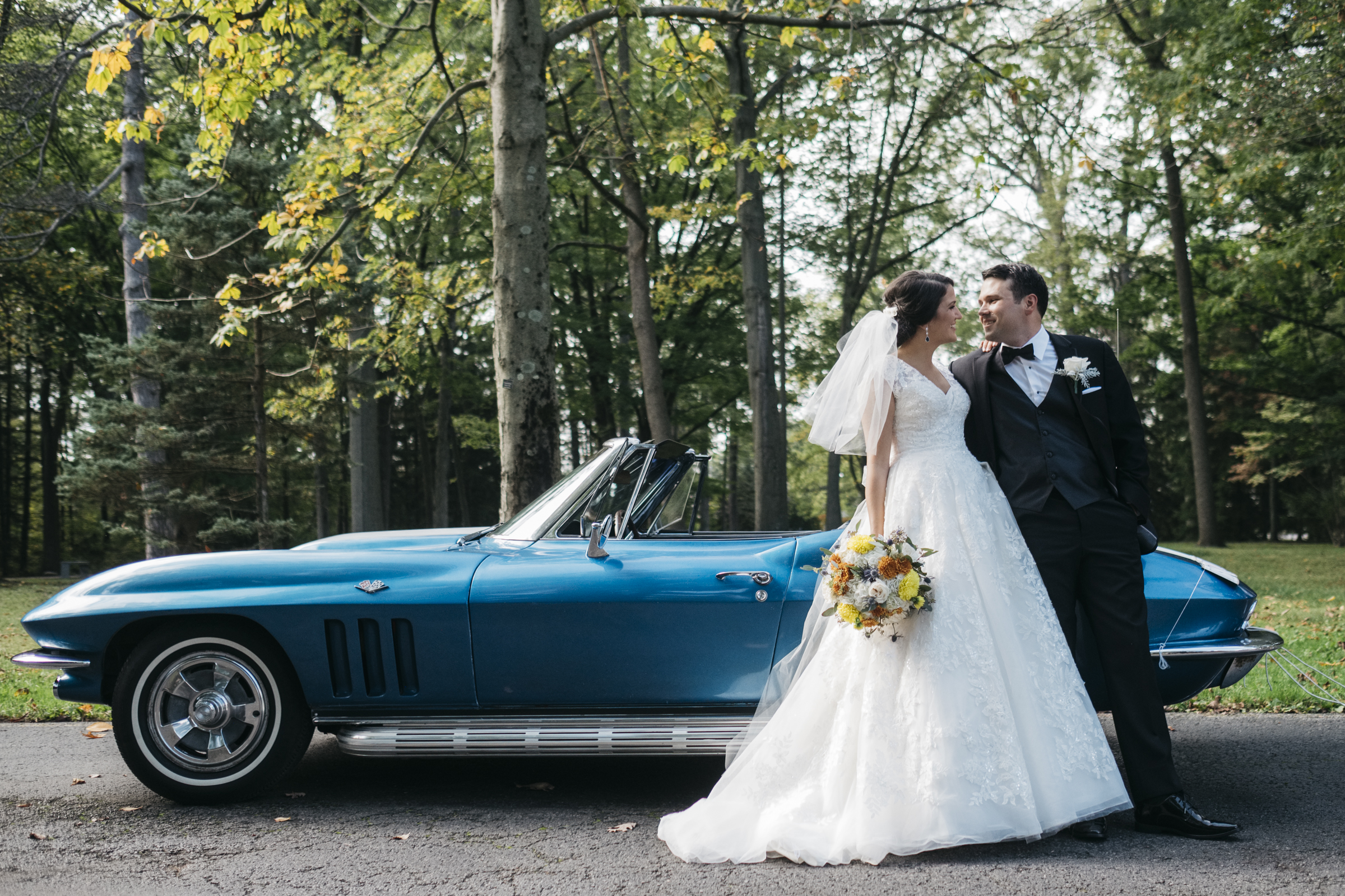 Bride and groom smile and sit on car at park in Fremont Ohio