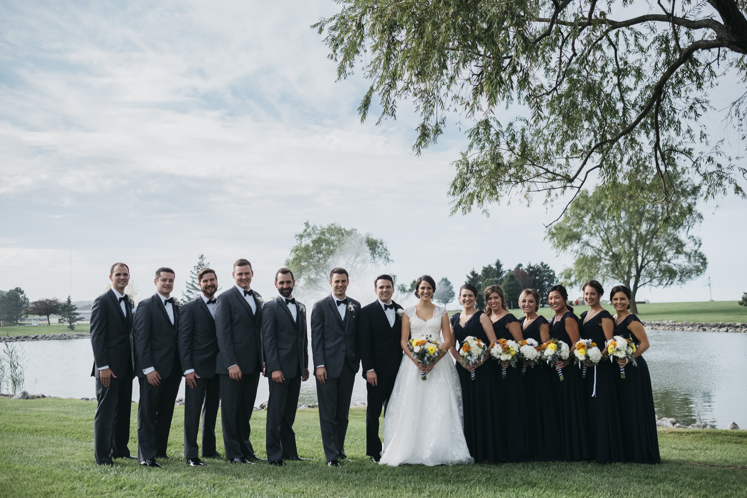 Bride and groom stand with their bridal party at the edge of the water in Maumee Ohio