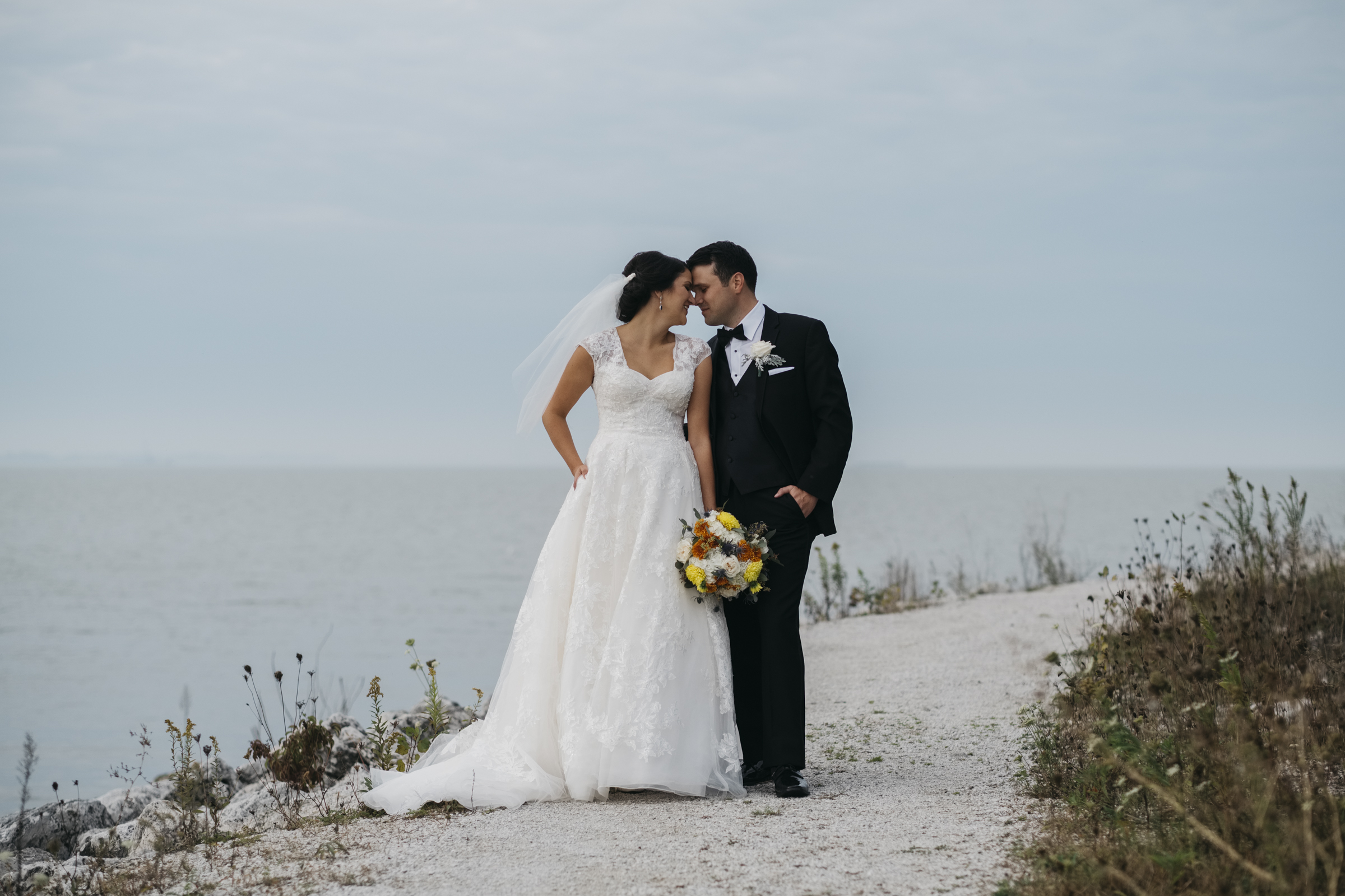 Bride and groom stand at the edge of the water for their nautical vintage themed wedding in Northern Ohio