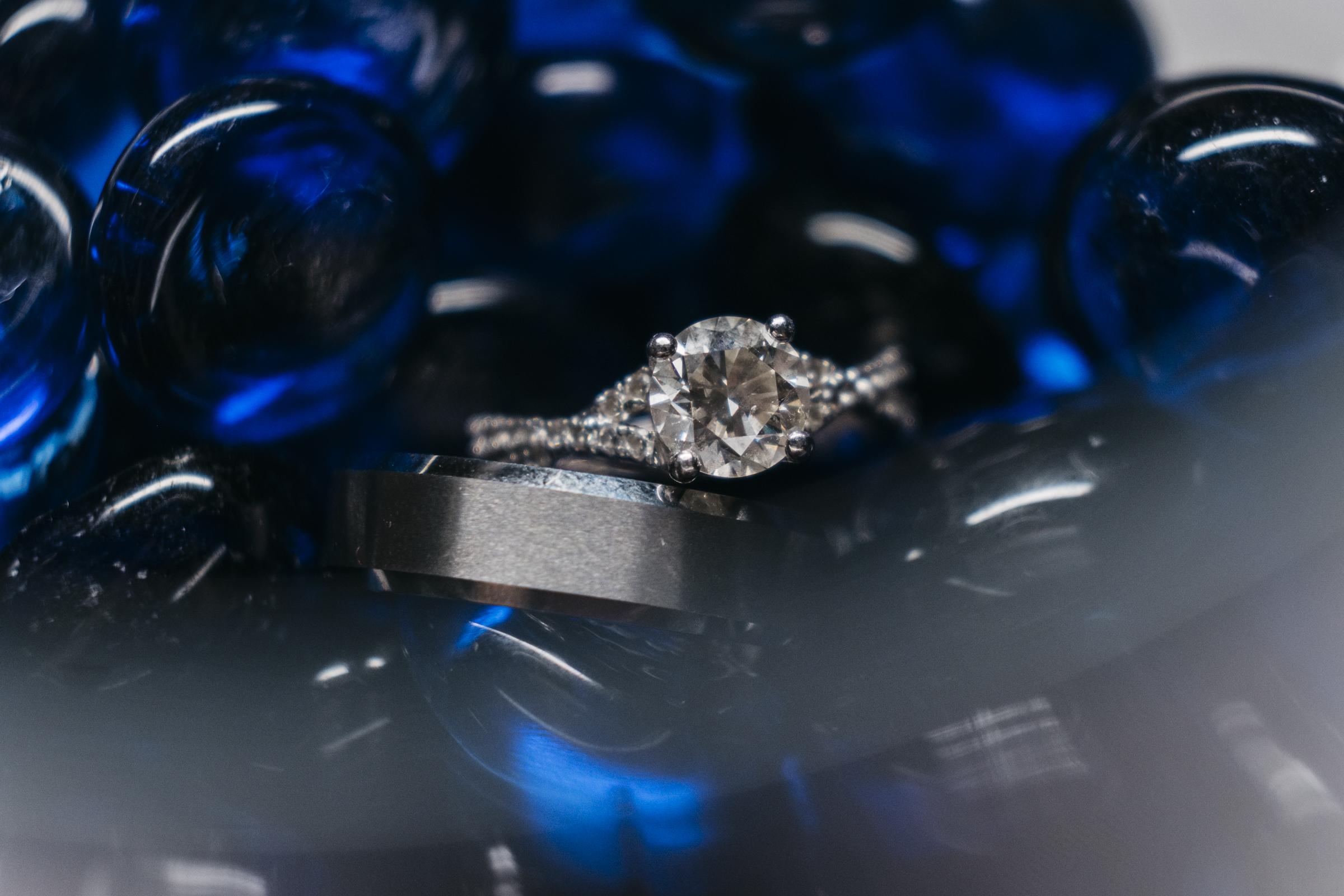 Wedding ring photo inspiration as wedding rings sit in blue beads