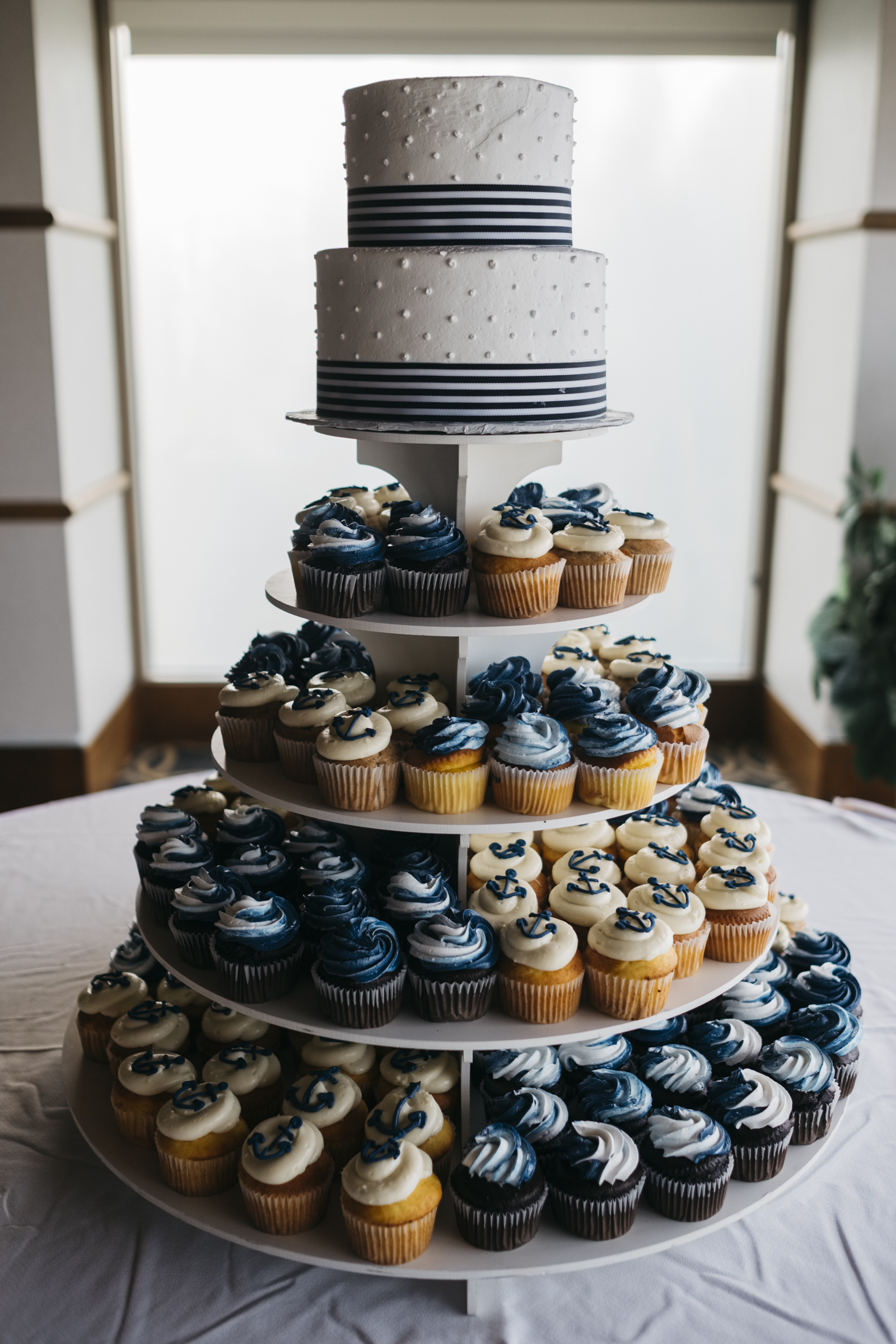 Navy blue and white anchor cupcakes surround wedding cake near Lake Erie wedding reception