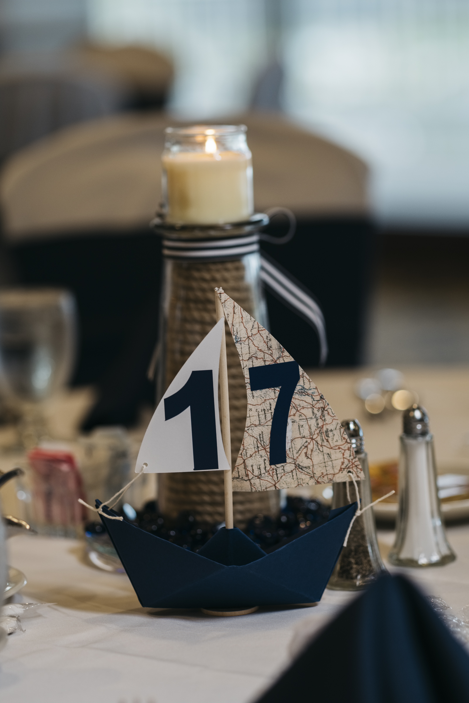 A little paper boat makes a perfect piece of wedding reception decor for lakeside nautical wedding