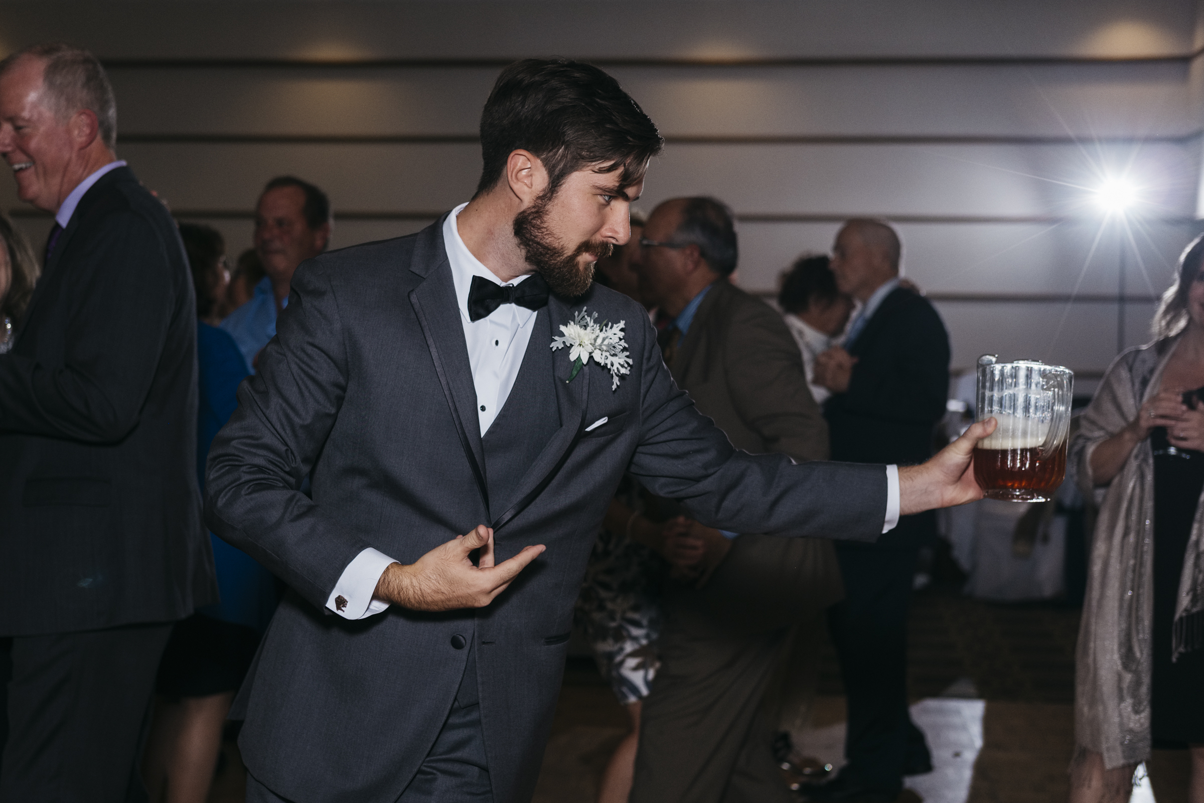 Groomsman dances with a pitcher of beer for a funny photo at wedding reception in Ohio