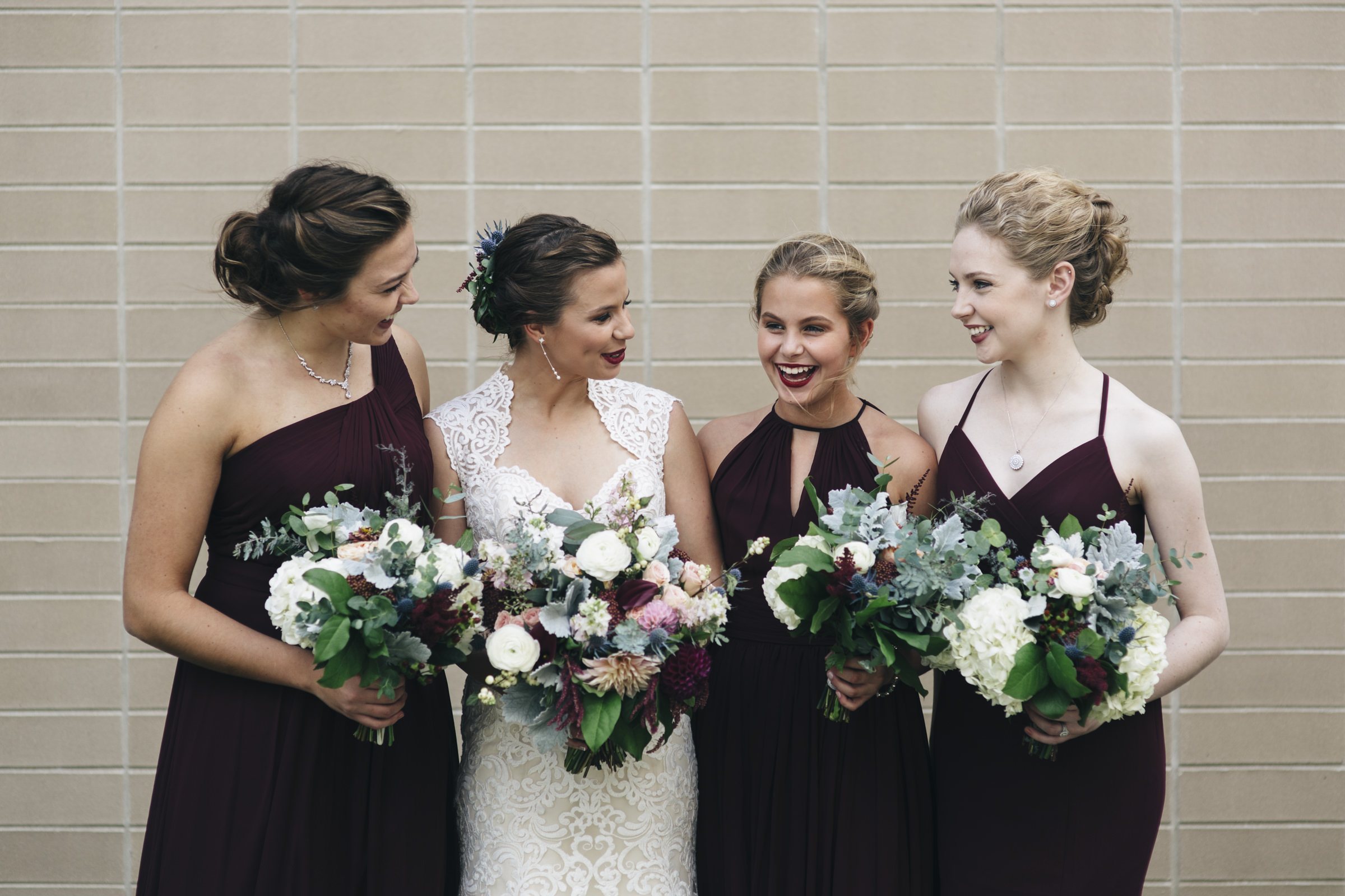 Bridesmaids smile and laugh with the bride before her wedding ceremony