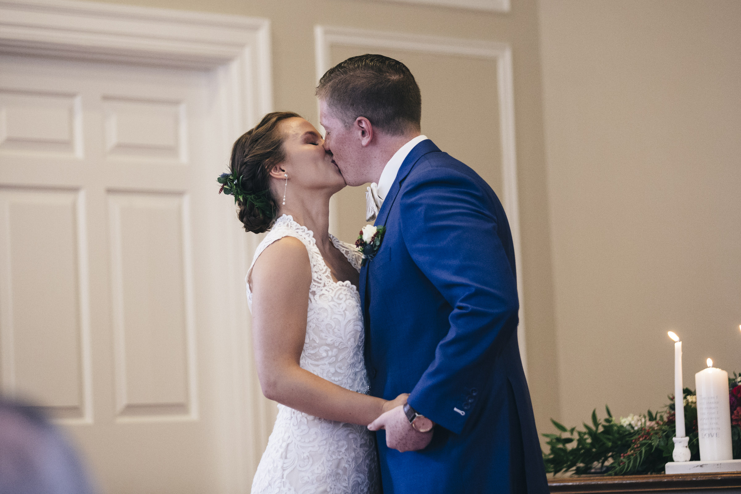 Bride and groom kiss during their wedding ceremony at Prout Chapel