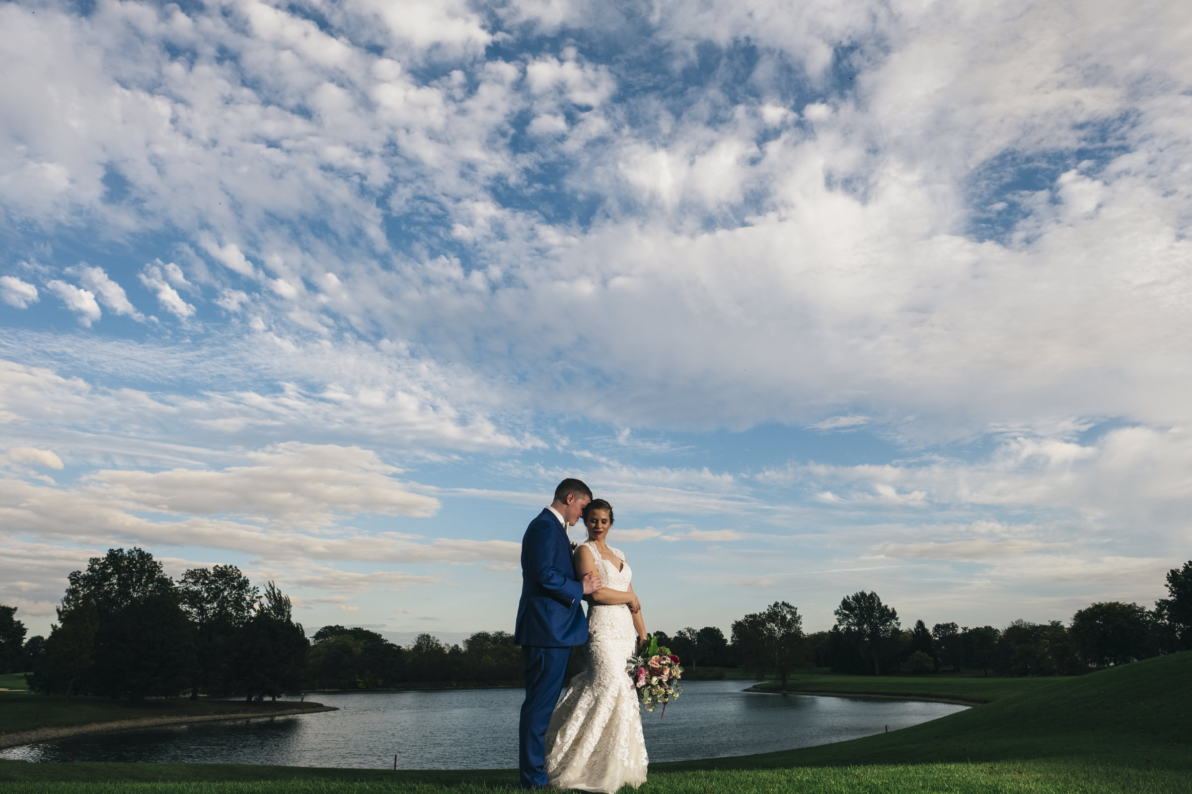 Bride and groom stand lakeside at Belmont Country Club in Perrysburg Ohio