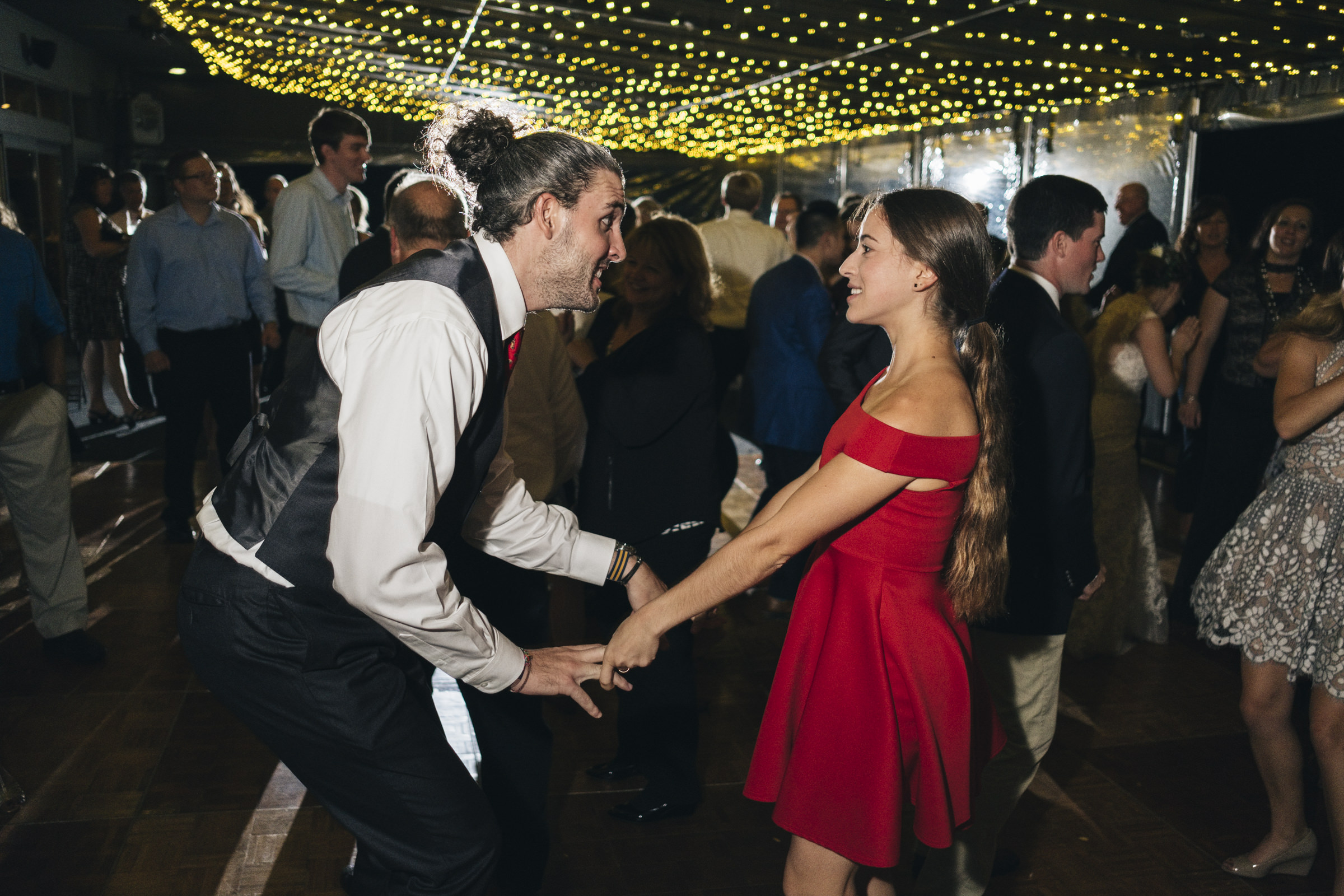 Guests of the bride and groom dance at their wedding reception in a bright red dress