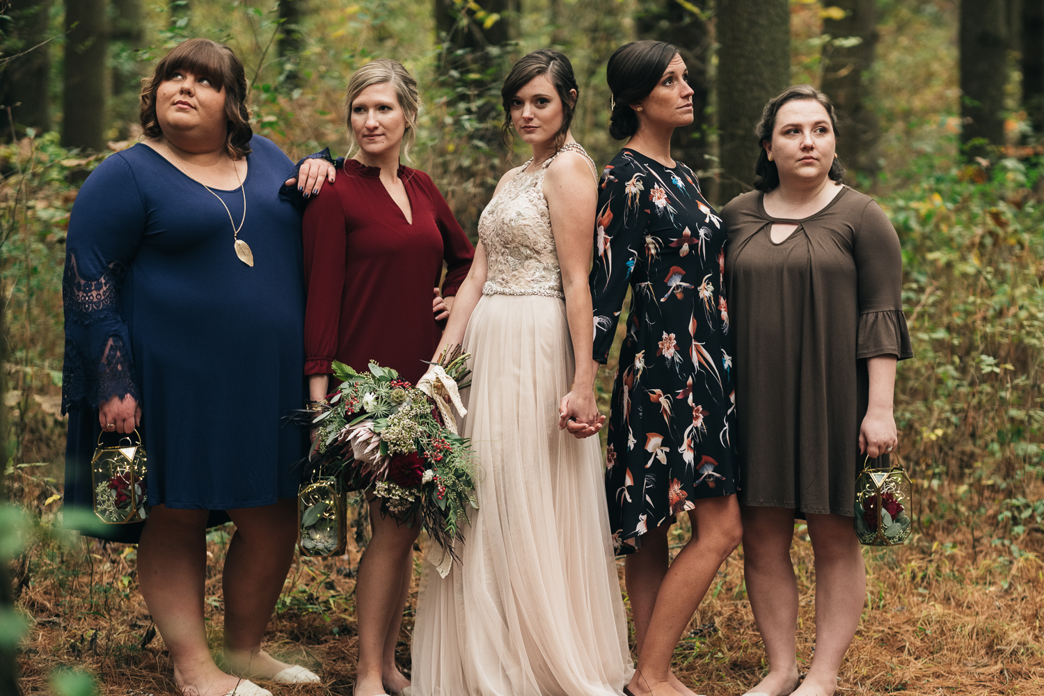 The bride stands with her bridesmaids in mix matched dresses at Oak Openings park in northwest Ohio for her fall wedding
