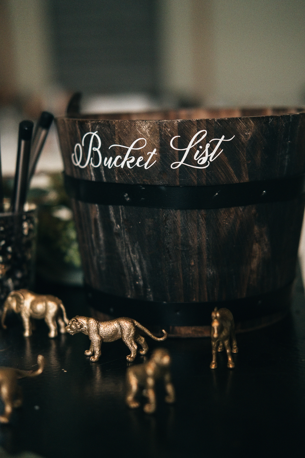 A bucket list bucket surrounded by animals sits outside wedding reception for guests