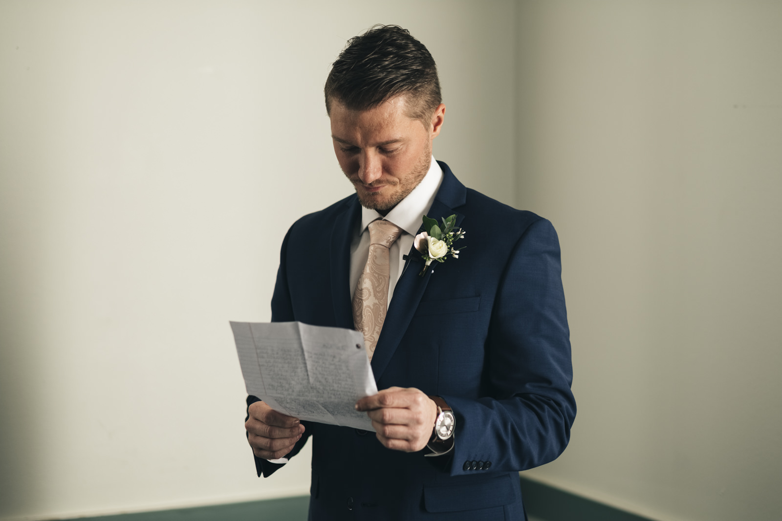 Groom reading letter from his bride before ceremony.