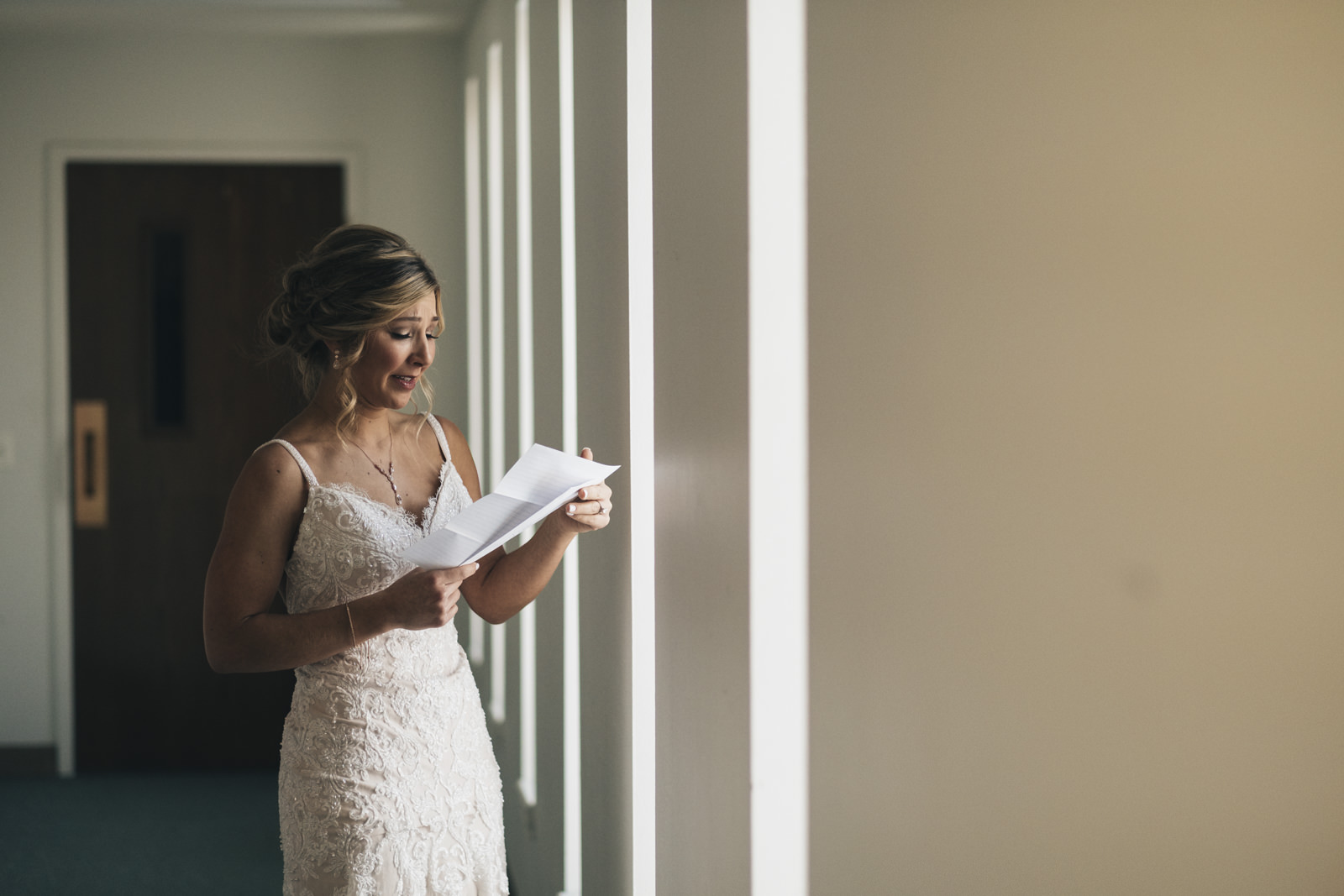 Emotional bride reads letter from her groom before the wedding ceremony.
