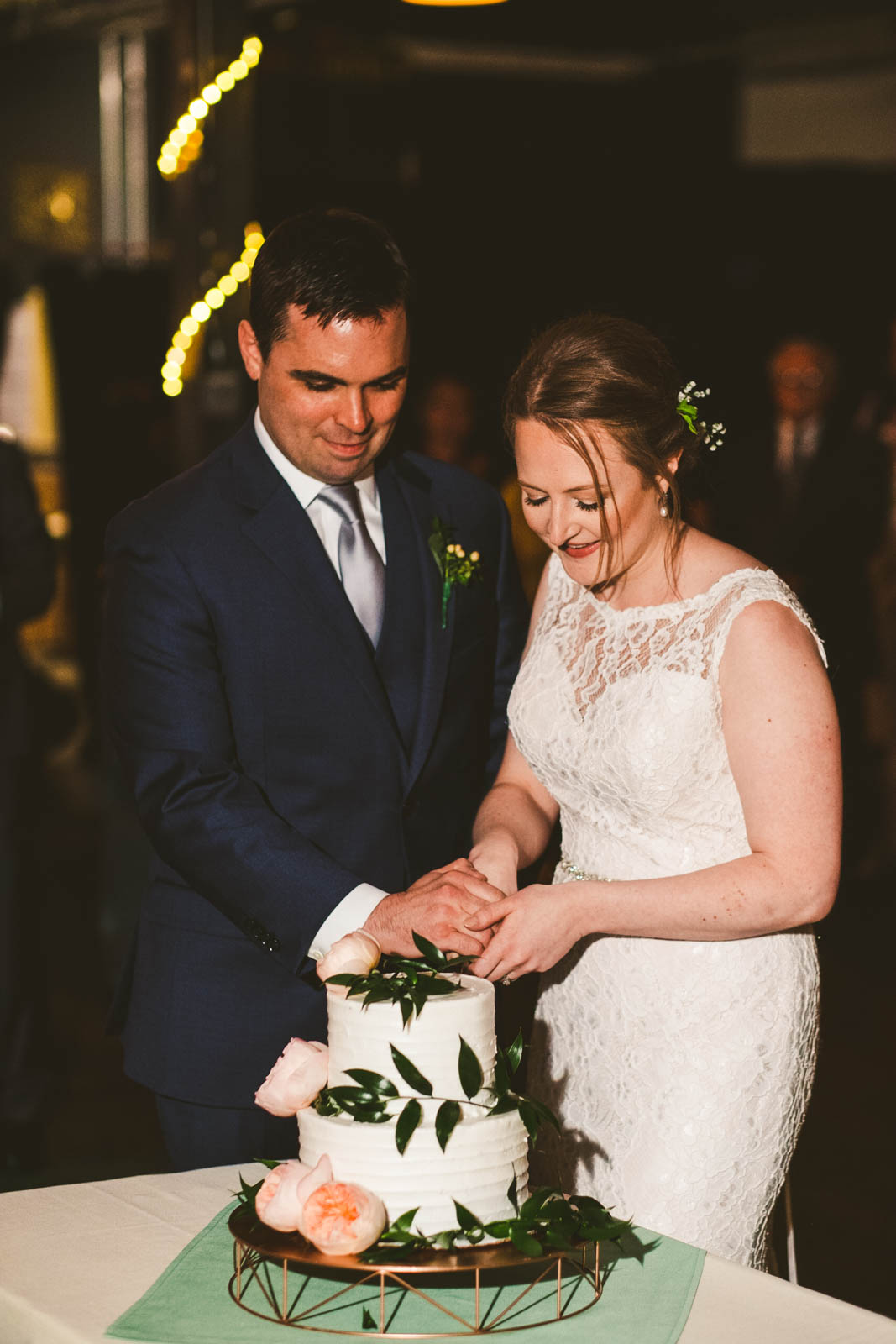 Toledo Wedding Photographers Capture Couple Cutting Cake at Reception at Maumee Bay Brewing Company