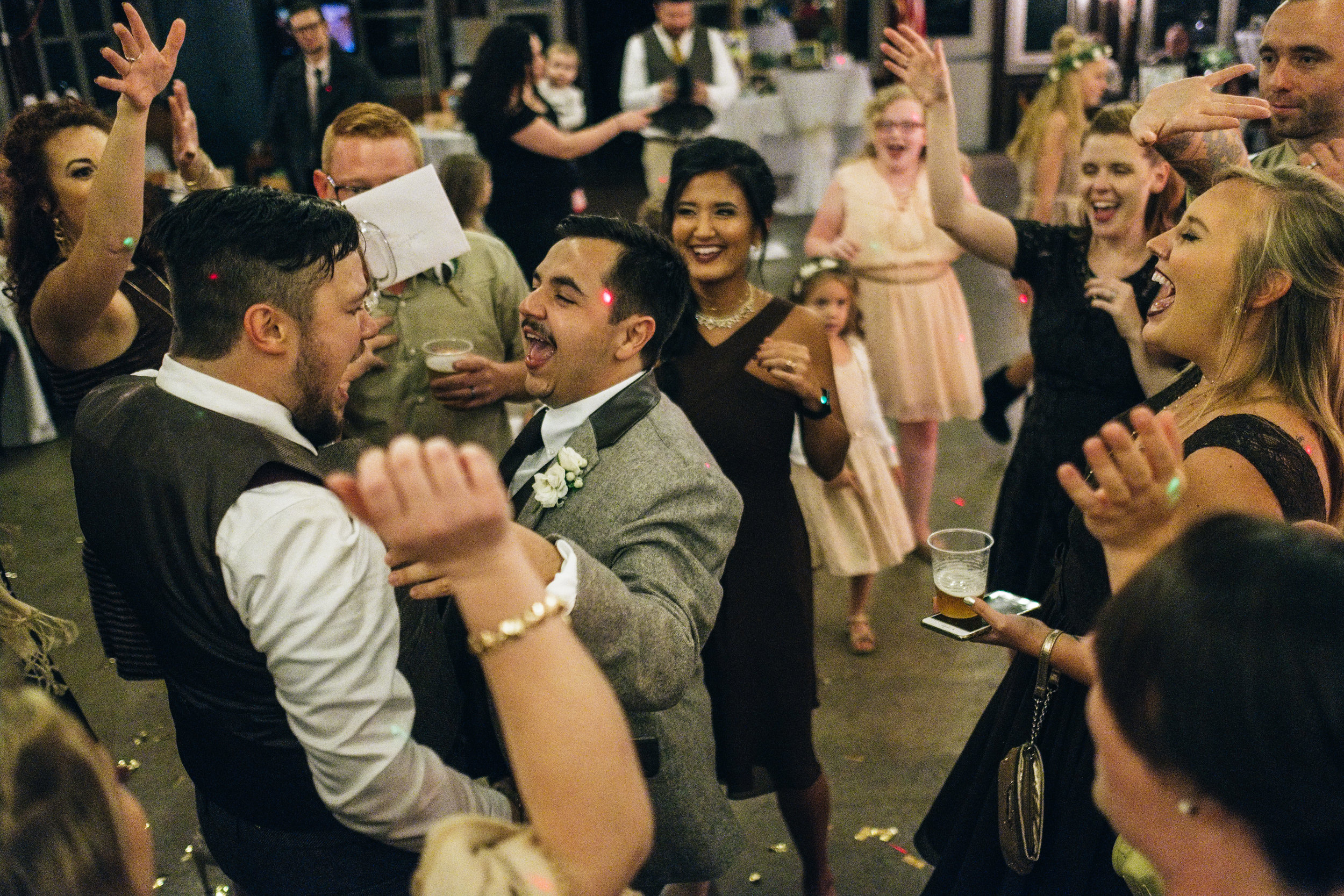 Same Sex Couples Dances with Guests at Wedding Reception in Cabin at Wayne Lakes Michigan with Toledo Wedding Photographers