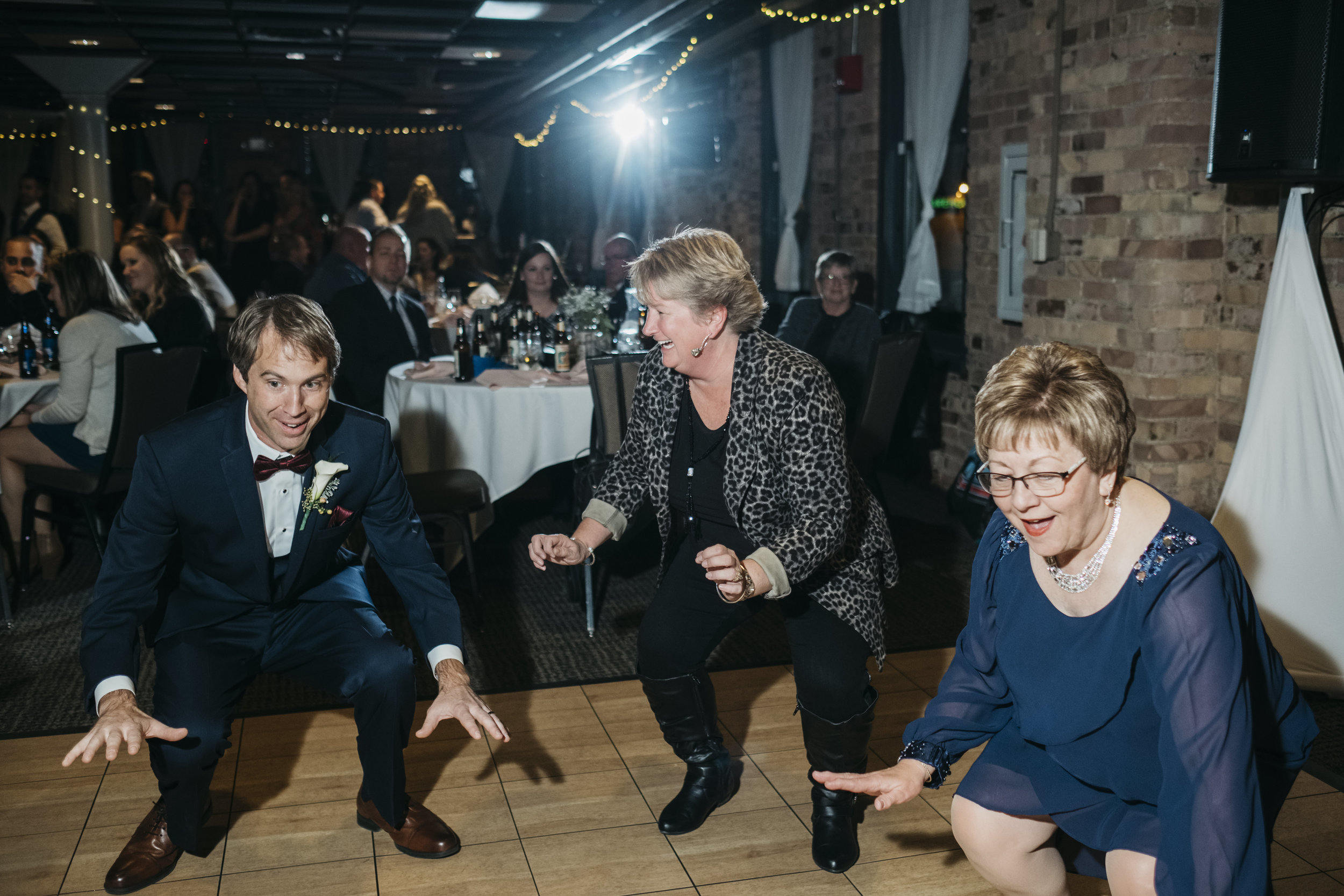 Guests and Groom Dance to Music on Dancefloor at Reception in Toledo Ohio with Wedding Photographers