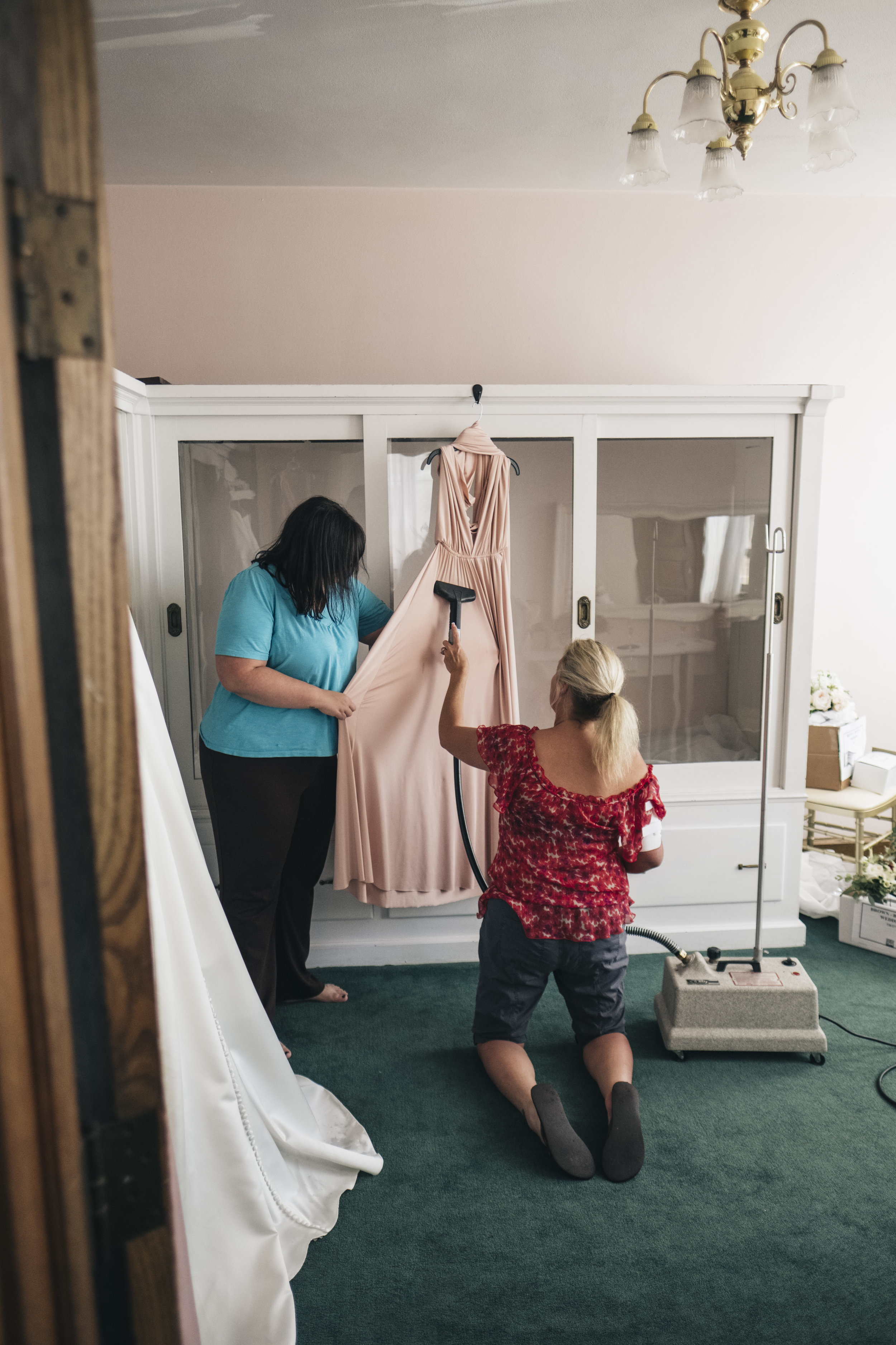Mother of the Bride Steams Wedding Dress before Toledo Ohio Wedding with Photographers