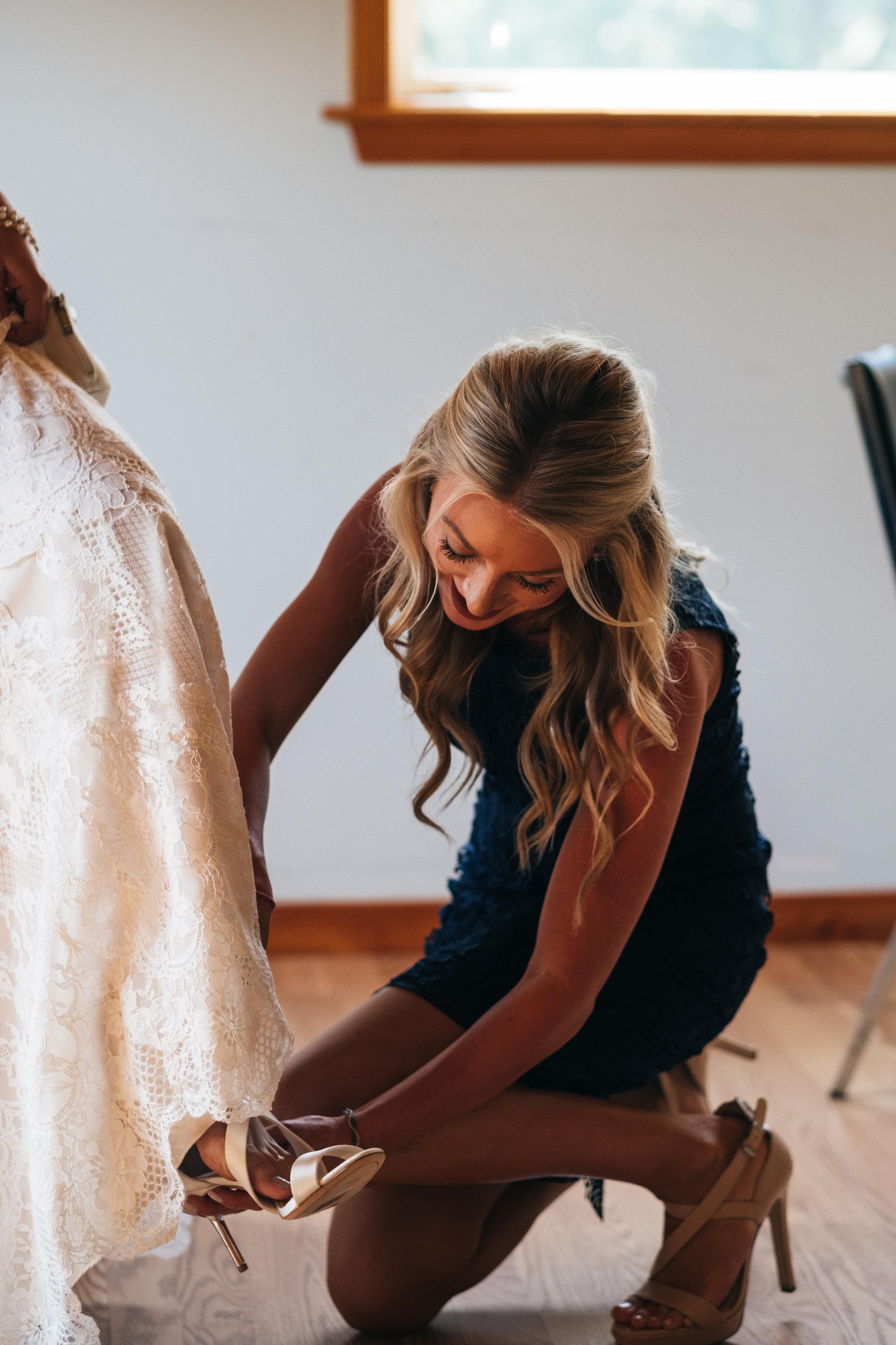 Maid of Honor Helps Bride put on Wedding Shoes for Toledo Ohio Wedding