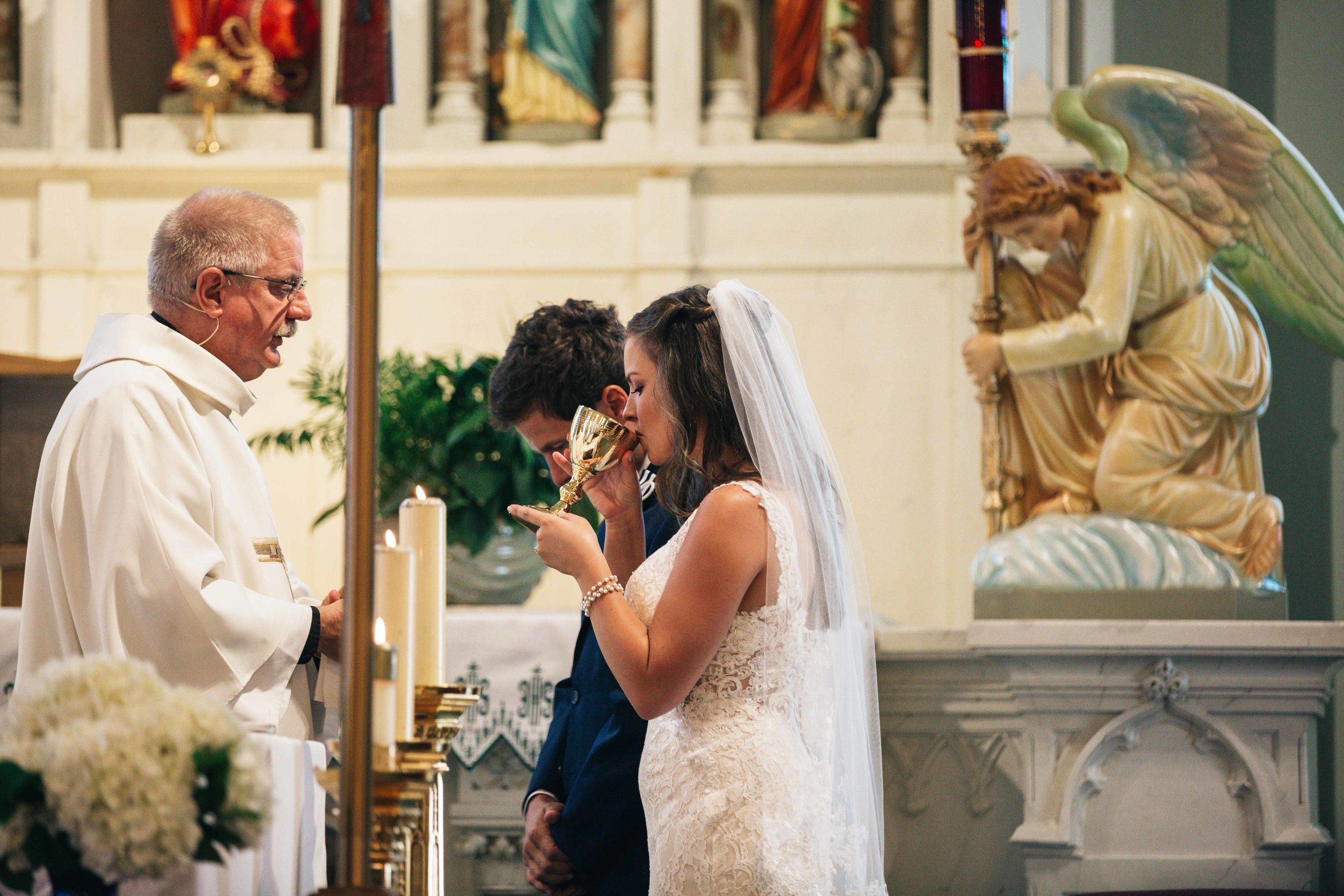 Bride and Groom from Toledo Ohio take Communion at Wedding for Unity with Photographers from Ohio
