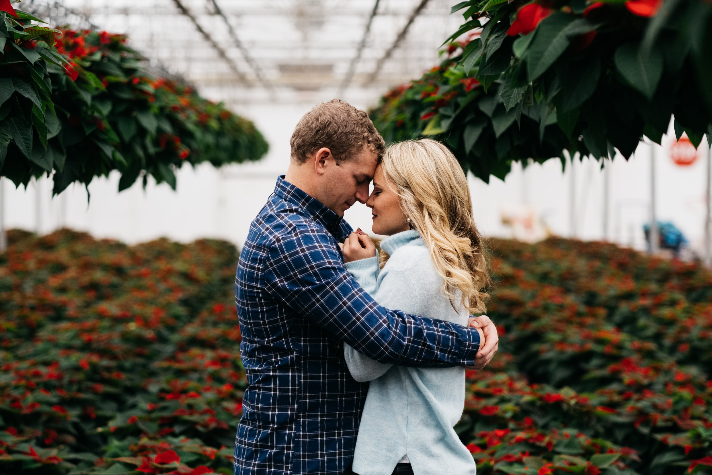 Couple from Toledo Ohio in Greenhouse for Engagement Session with Wedding Photographers