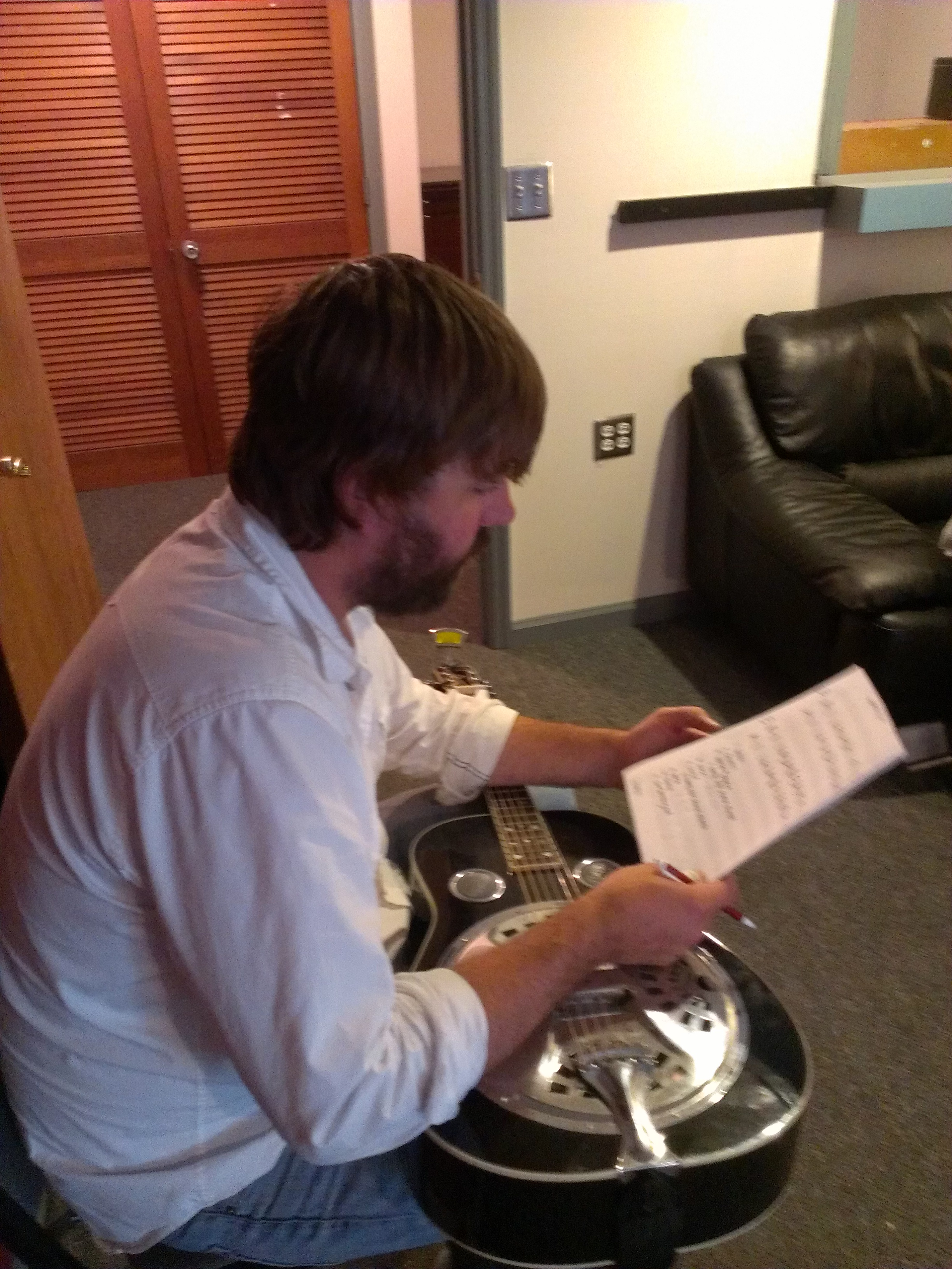 Jay looking at chord charts as his dobro looks on.