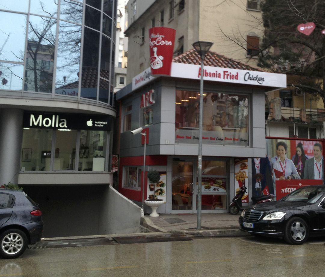"Two things are funny in this picture I took while in Tirana.  One is the obvious rip-off of KFC (logo, fonts and all).  The other is to the left - the supposed authorized reseller of Apple products, the name of the store is ""Molla"" - Albanian for Apple.  Now you know."