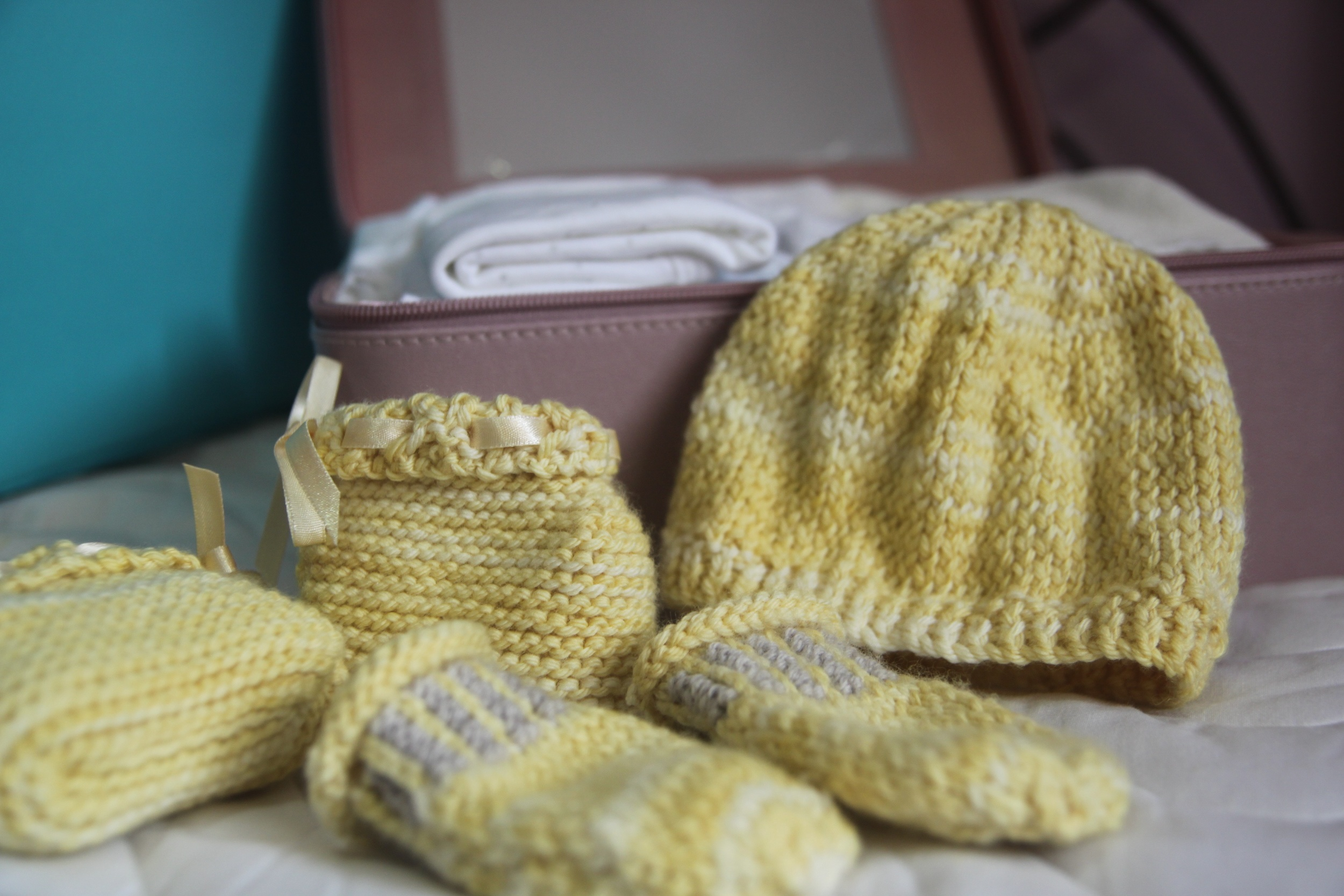 A small suitcase of baby clothes and blanket plus my hand-knitted hat, mittens and baby boots.
