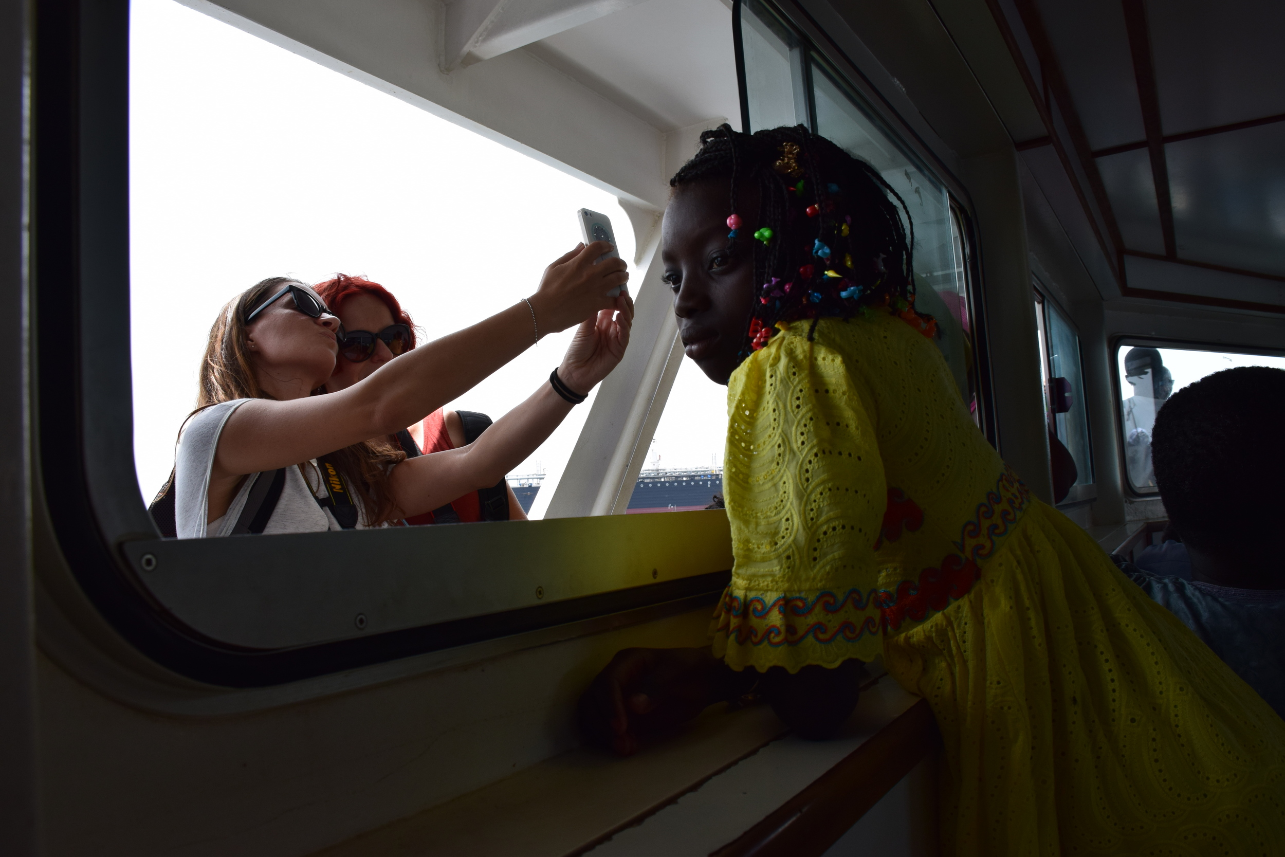 On the ferry from Dakar to Gorée, I was struck by the juxtaposition of the little girl's thoughtfulness and brightly colored clothing, and tourist selfies. There is much to learn from children.
