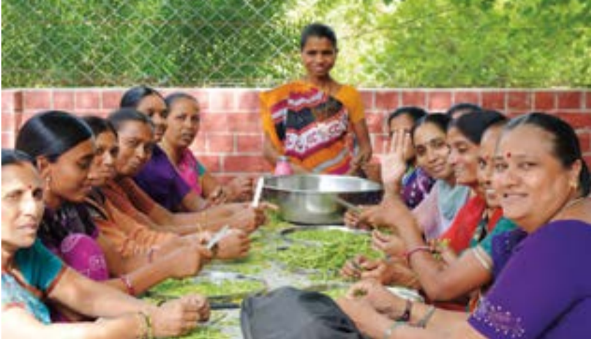 Women working at ESI gather to chat and prepare vegetables for the evening meal.