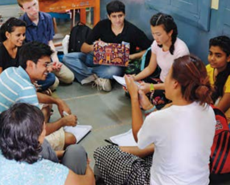 At a government-funded elementary school on the outskirts of Ahmedabad, Niswarth students John Gorton '15(top left), Kimberly Dawes, PEA '15 (in pink), and Rhaime Kim '15 (in white) and their Riverside School peersdiscuss what they learned from observations and interviews.