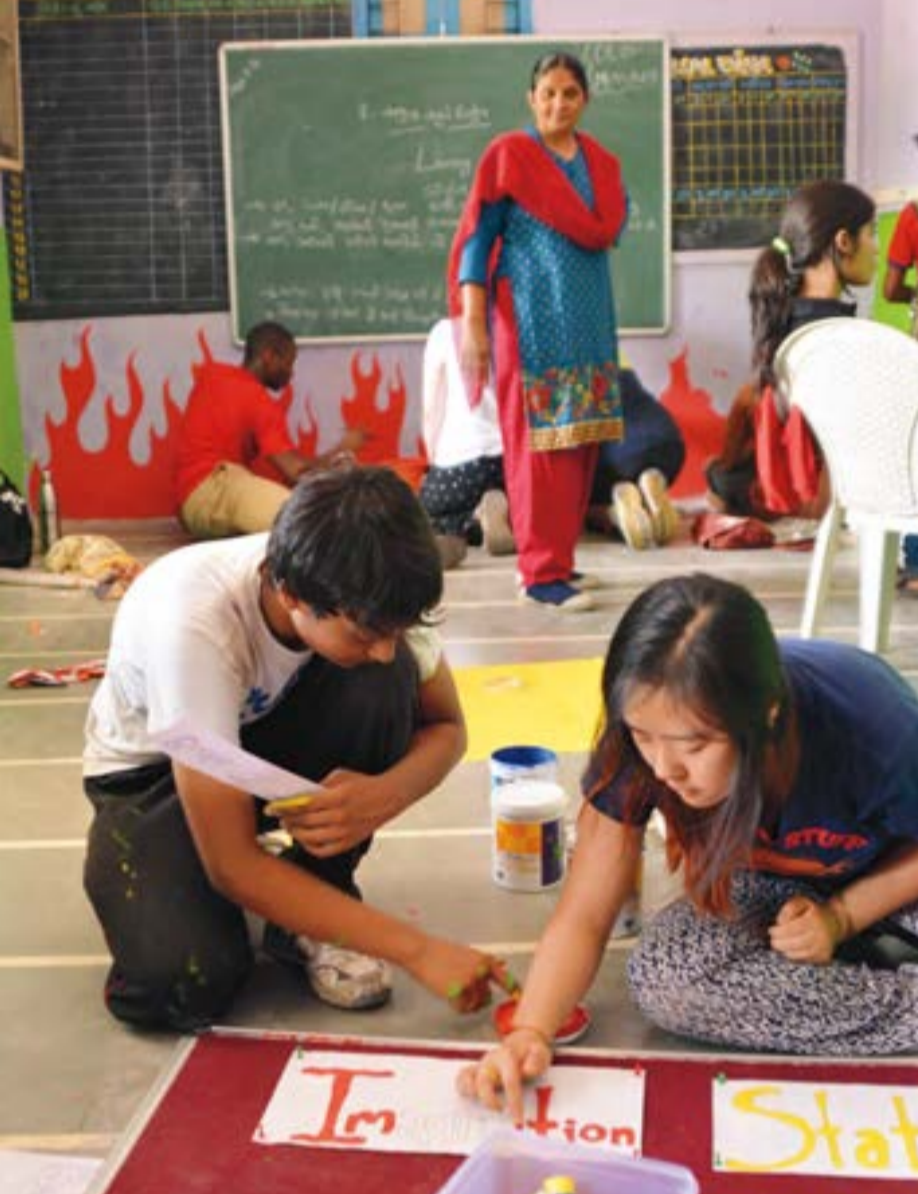 Nick Madamidola, PEA '16(back left), and Jenny Wang '16 (rightforeground) work with Riverside Schoolstudents to make the government school'ssparse library more colorful and inviting.