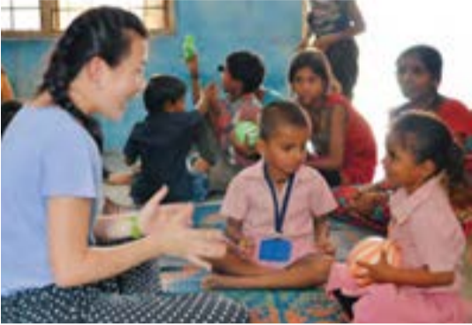 Gokul Pura, an anganwadi supported by Setco Foundation,has two Hindu temples, a community well, and numerous cows andwater buffalo. Villagers grow okra and mangos. Here, Kimberly  Dawes, PEA '15, plays catch with two preschoolers.