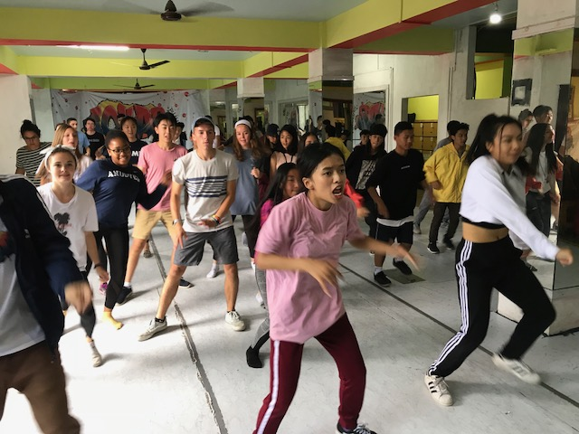 "One of the lead dancers (center in pink) from GOKAB (meaning ""Opportunity"" in dzongkha) teaches ELC and Andover students a hip-hop dance in their downtown Thimphu studio -- so far the only dance studio in Bhutan. Dance, they explain, is a healthy outlet for youth to express themselves."