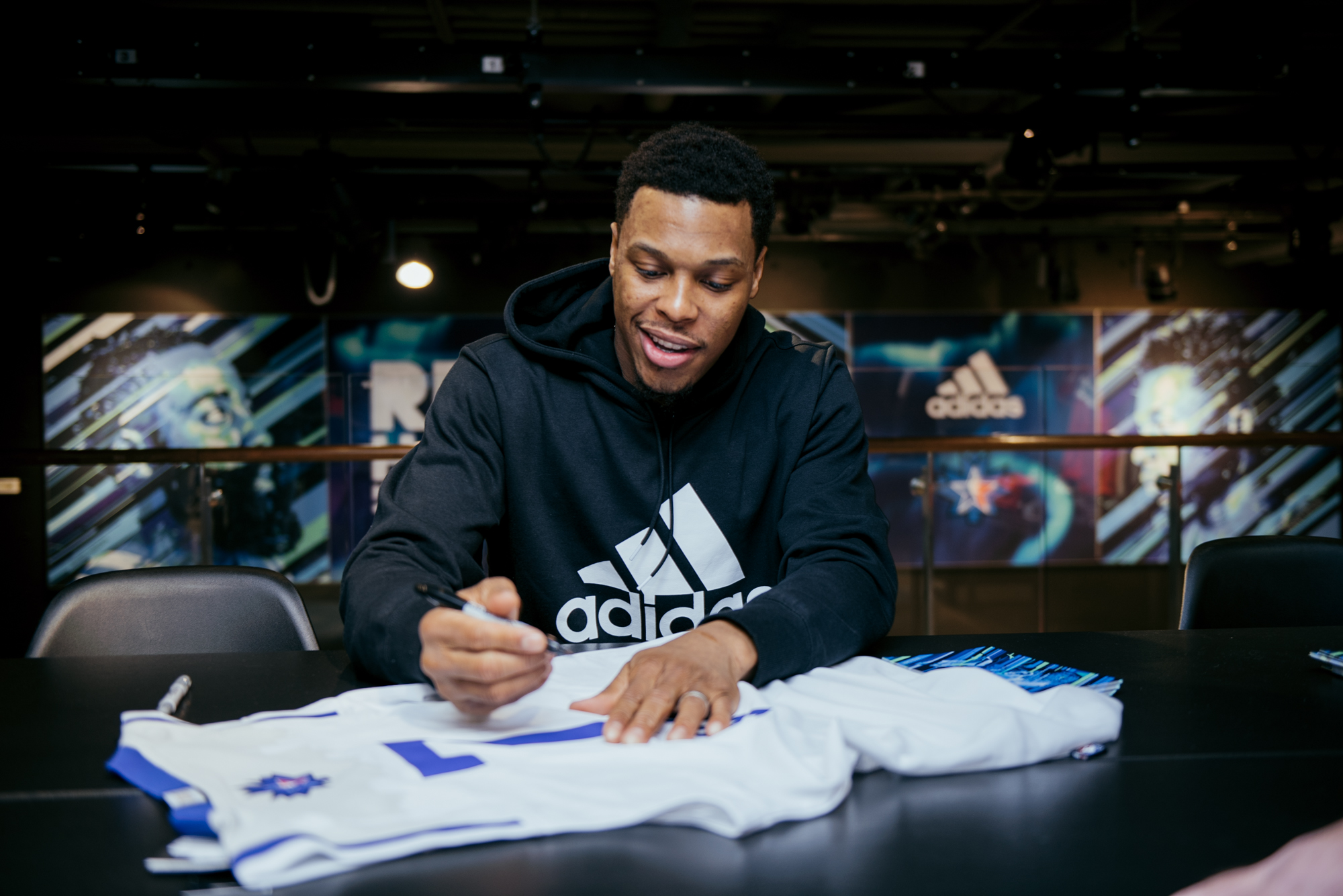 Kyle Lowry of the Toronto Raptors signs jerseys at the adidas flagship store in downtown Toronto.