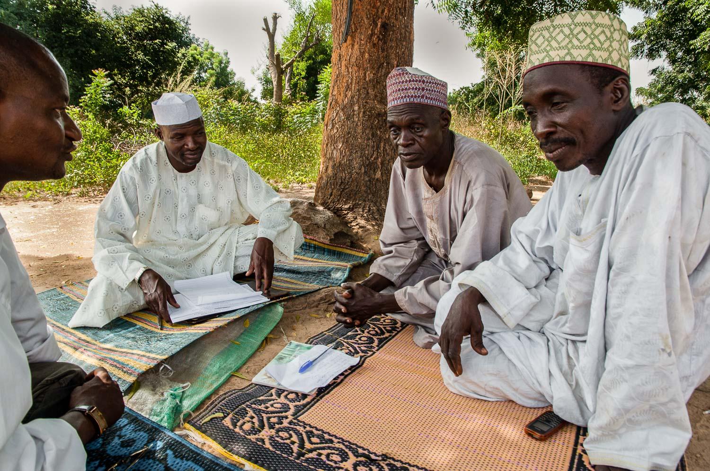 A census taker talking to village elders.