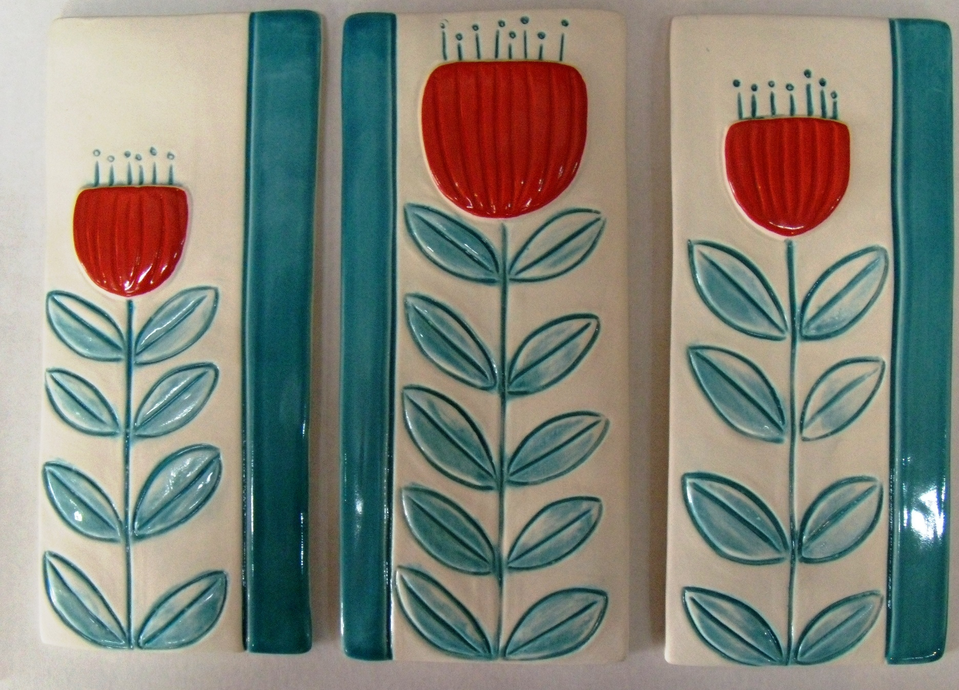 Pohutukawa tiles $99 White with turquoise and orange decoation. Each tile measures 100mm w x 230mm h. Comes boxed.