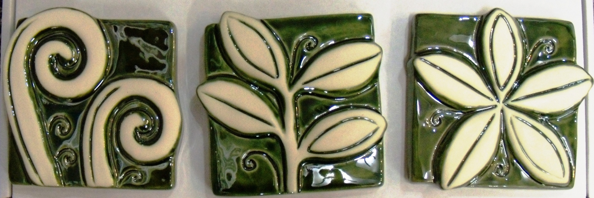 Vibrant N.Z. small $63 Set of 3 depicting Koru, frangipani and Puriri leaves. Each tile measures approx 100mm square. Comes boxed