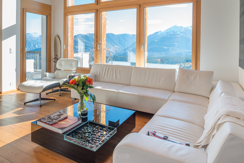 The high windows open the living room to a spectacular view of the mountains