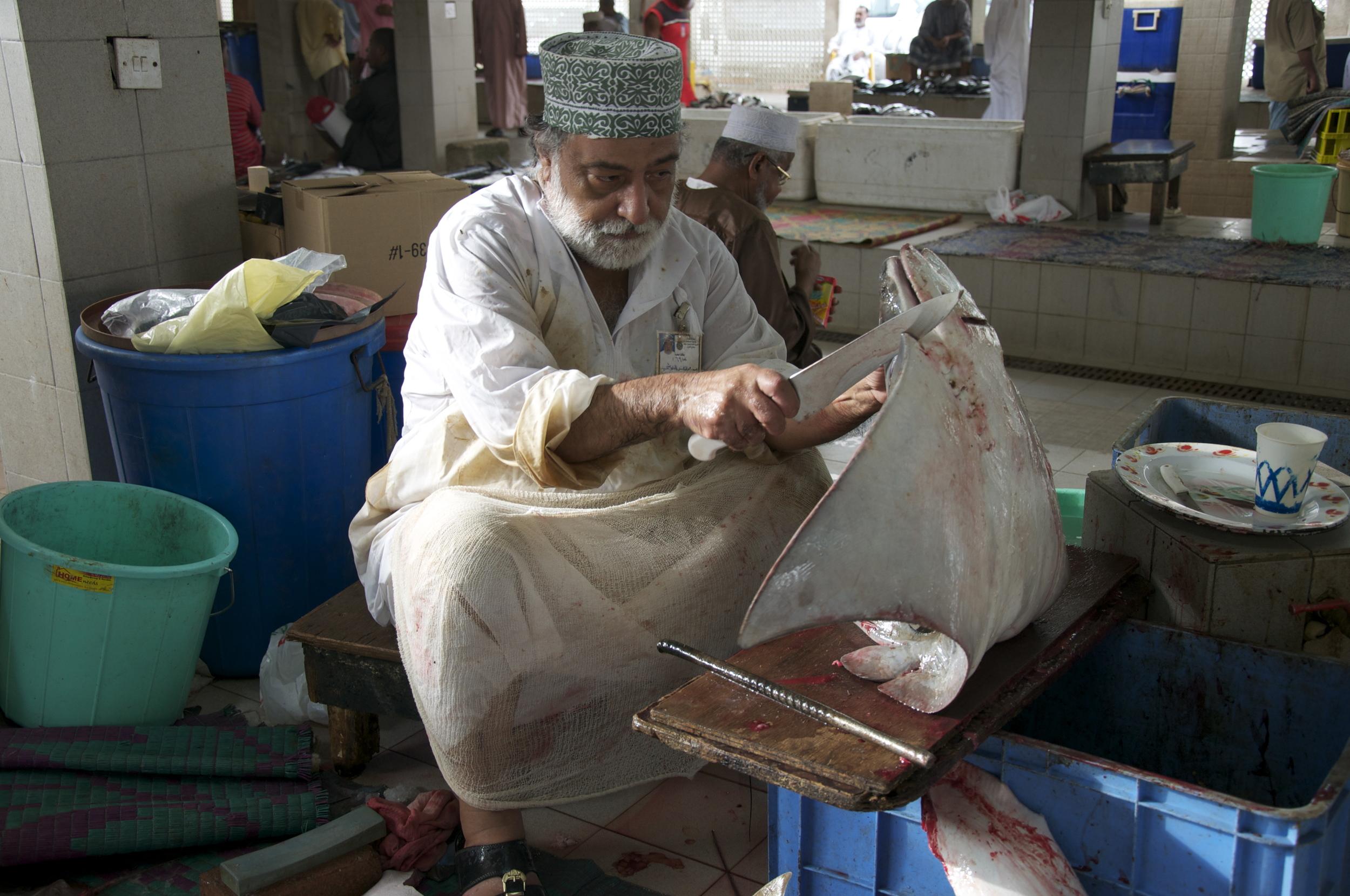 An Omani fisherman cuts skate wings. Photo copyright Meghan Miner Murray.