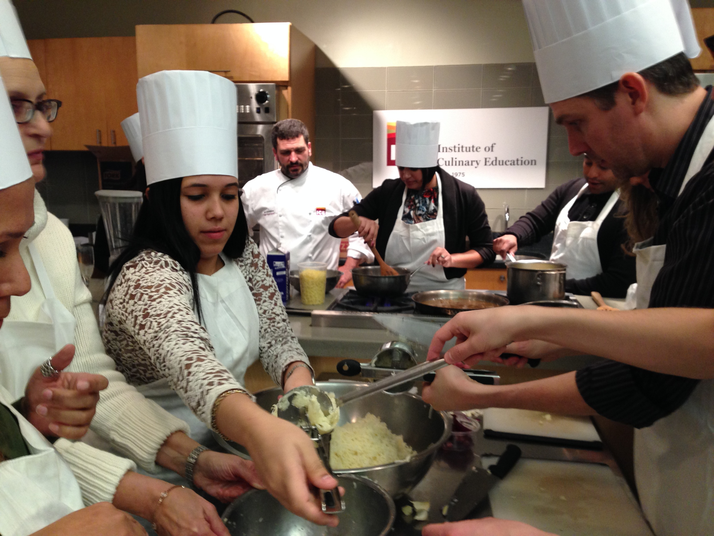 Stephanie Carril and Matt Bray in deep concentration as they prepare dinner as part of the annual firm holiday party/cooking lesson at the Institute of Culinary Education.